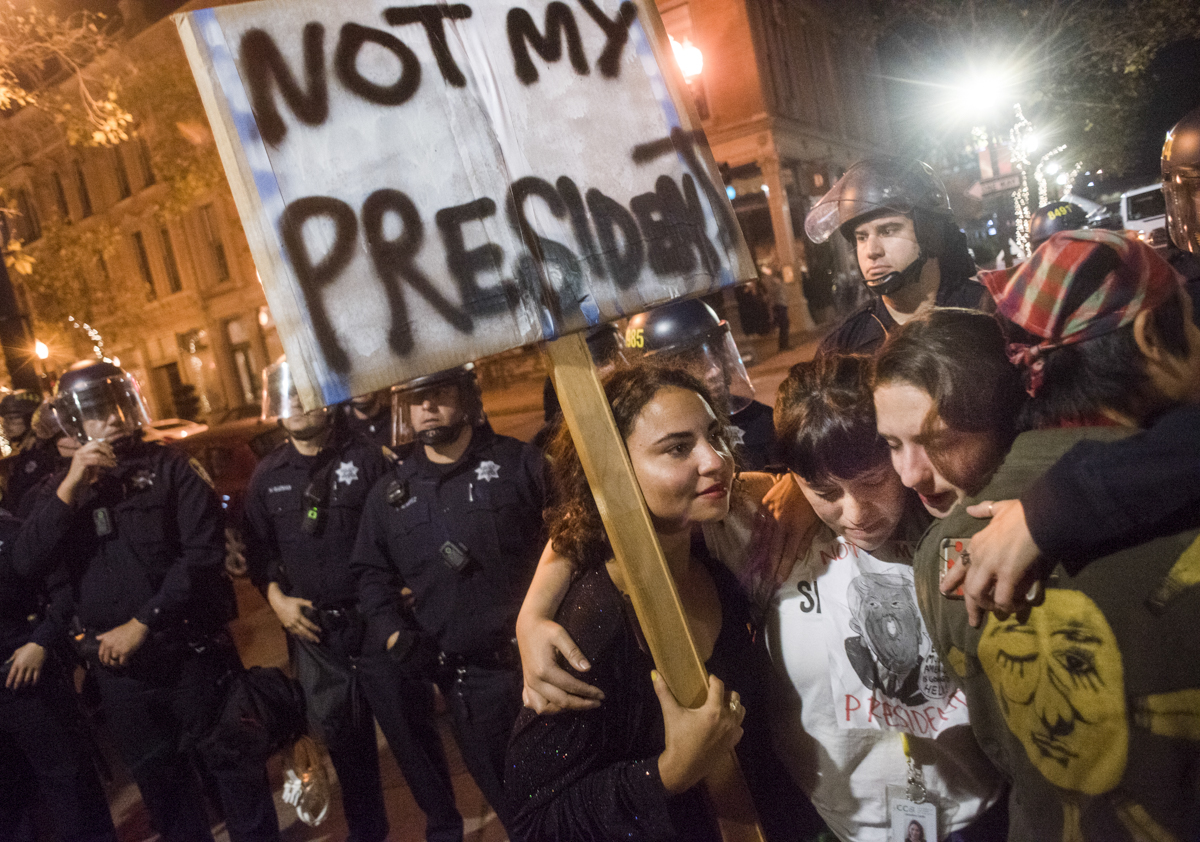 "Protesters embrace holding a sign that reads ""not my president"" as Oakland Police Department riot police attempt to break up an anti-Trump protest in downtown Oakland on November 9, 2016."