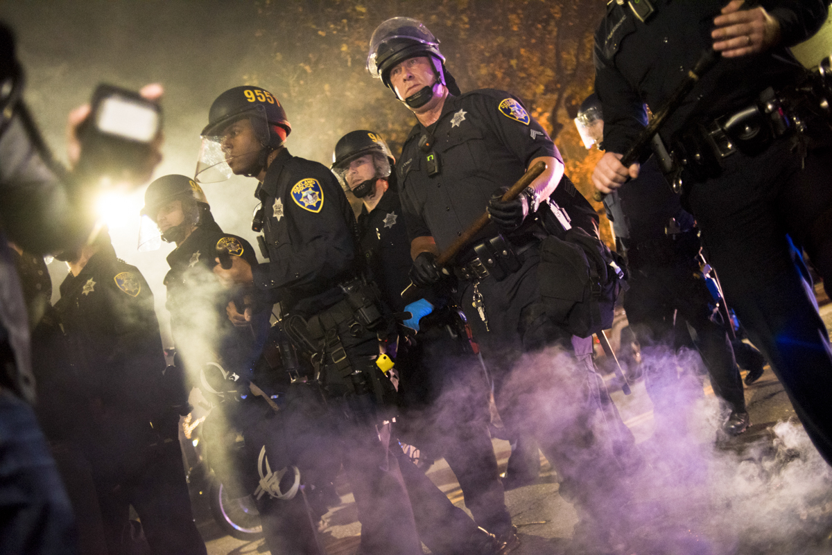 Oakland Police Department riot police push back protesters to get to an unlawful street fire during an anti-Trump protest in downtown Oakland on November 9, 2016.
