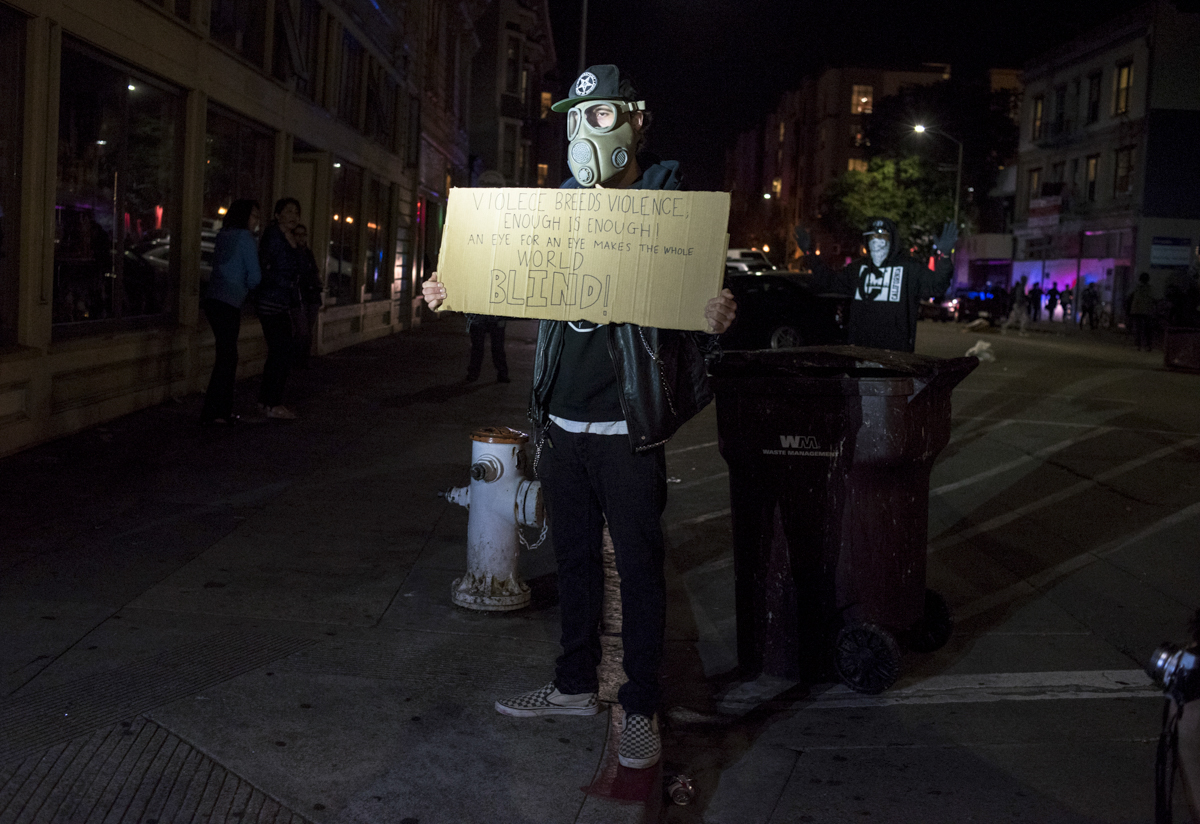 Nicholas Large of Clayton holds a sign at the row of Oakland Police Department riot police during an anti-Trump protest in downtown Oakland on November 9, 2016.