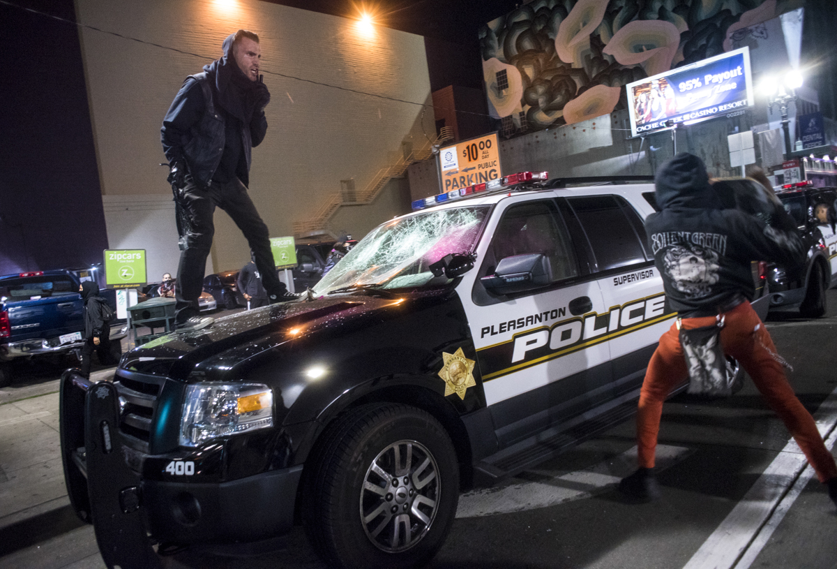 Anti-Trump protesters demolish a Pleasanton Police car in downtown Oakland on November 9, 2016. The peaceful protest escalated to property damage and street fires late into the night.