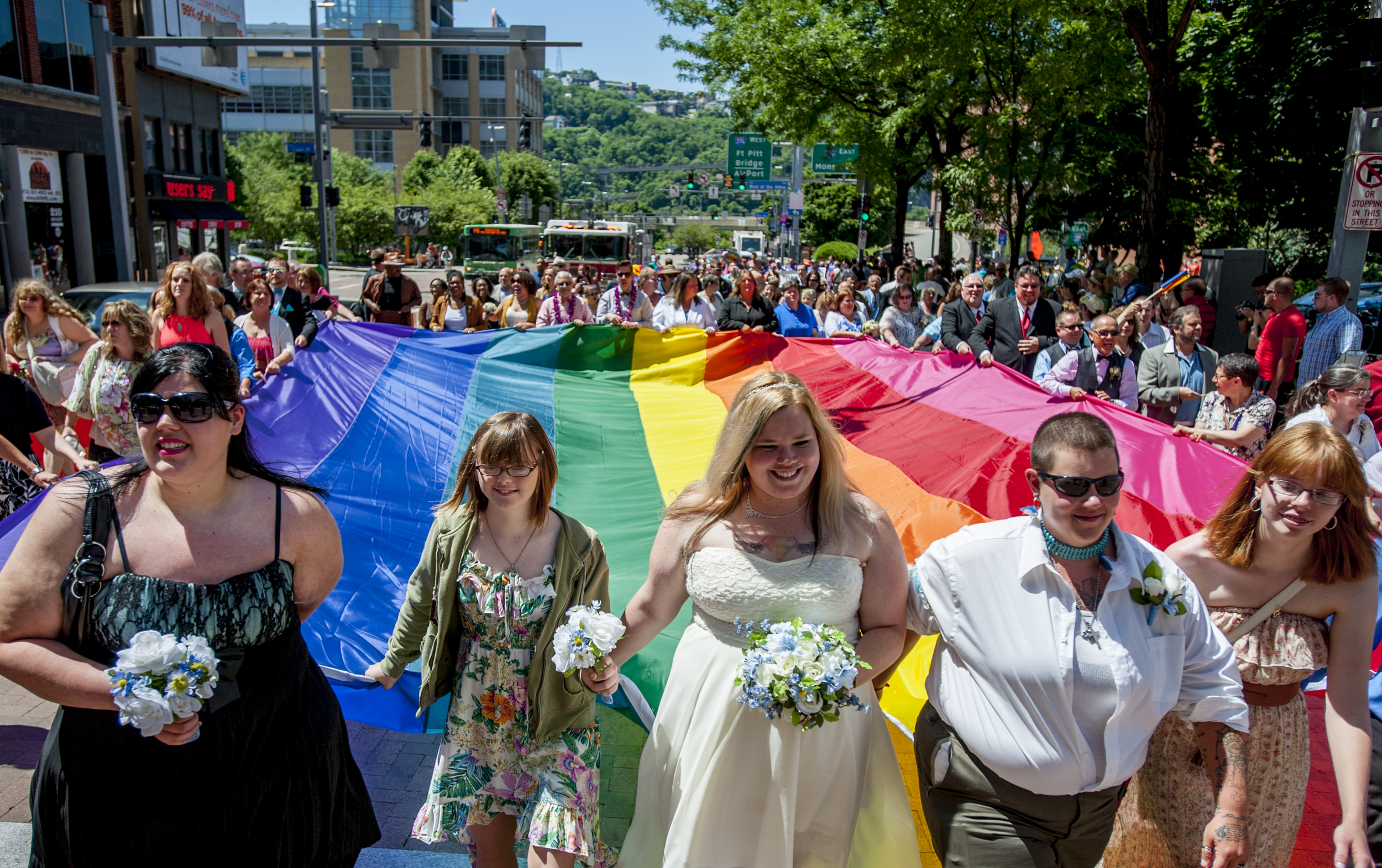 Just-married couples line the outside of a rainbow flag at the front of the 2015 Pittsburgh Pride Parade. The morning of the parade, 80 LGBTQ couples were married by Pittsburgh Mayor Bill Peduto at the city courthouse.