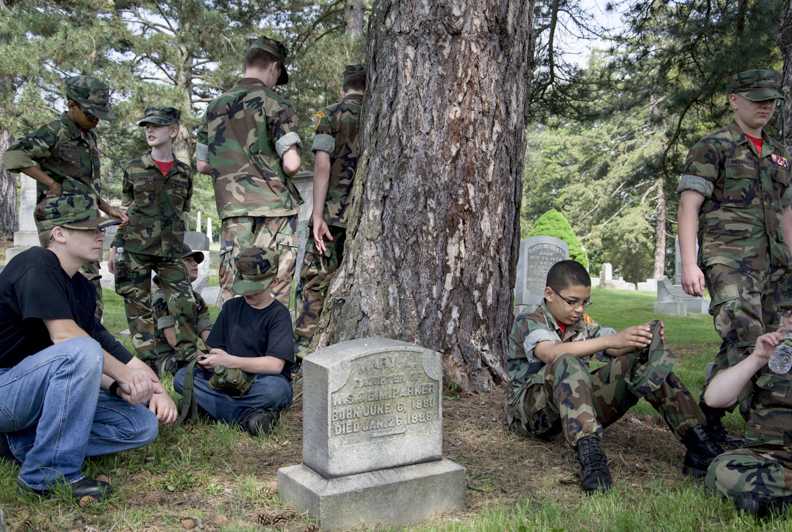 The Washington County Young Marines rest after placing flags on the gravestones of veterans.