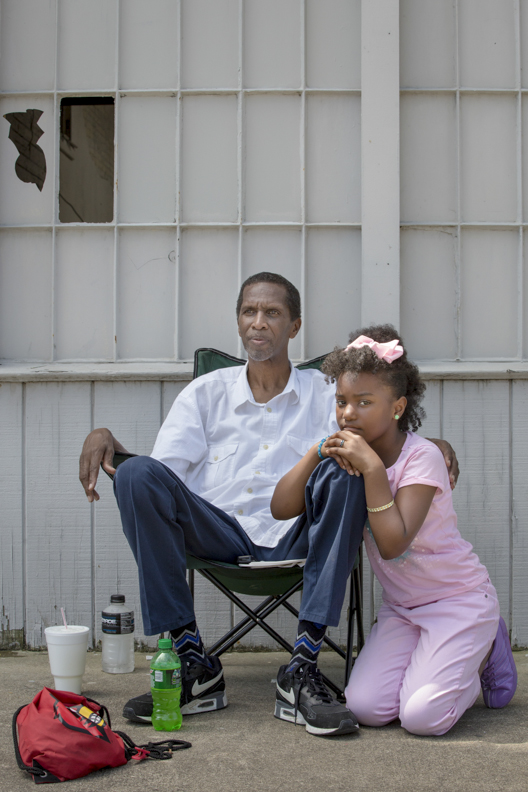 Donald Golightly and Jayla Hall, 9, wait along Broadway in Smoketown for the passing of Muhammad Ali's procession on June 10, 2016. Both are members of the Cable Baptist Church and came down with members of their congregation to witness the procession.