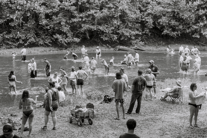 Patrons of the Nelsonville Music Festival wade in the Hocking River. Nelsonville, OH.