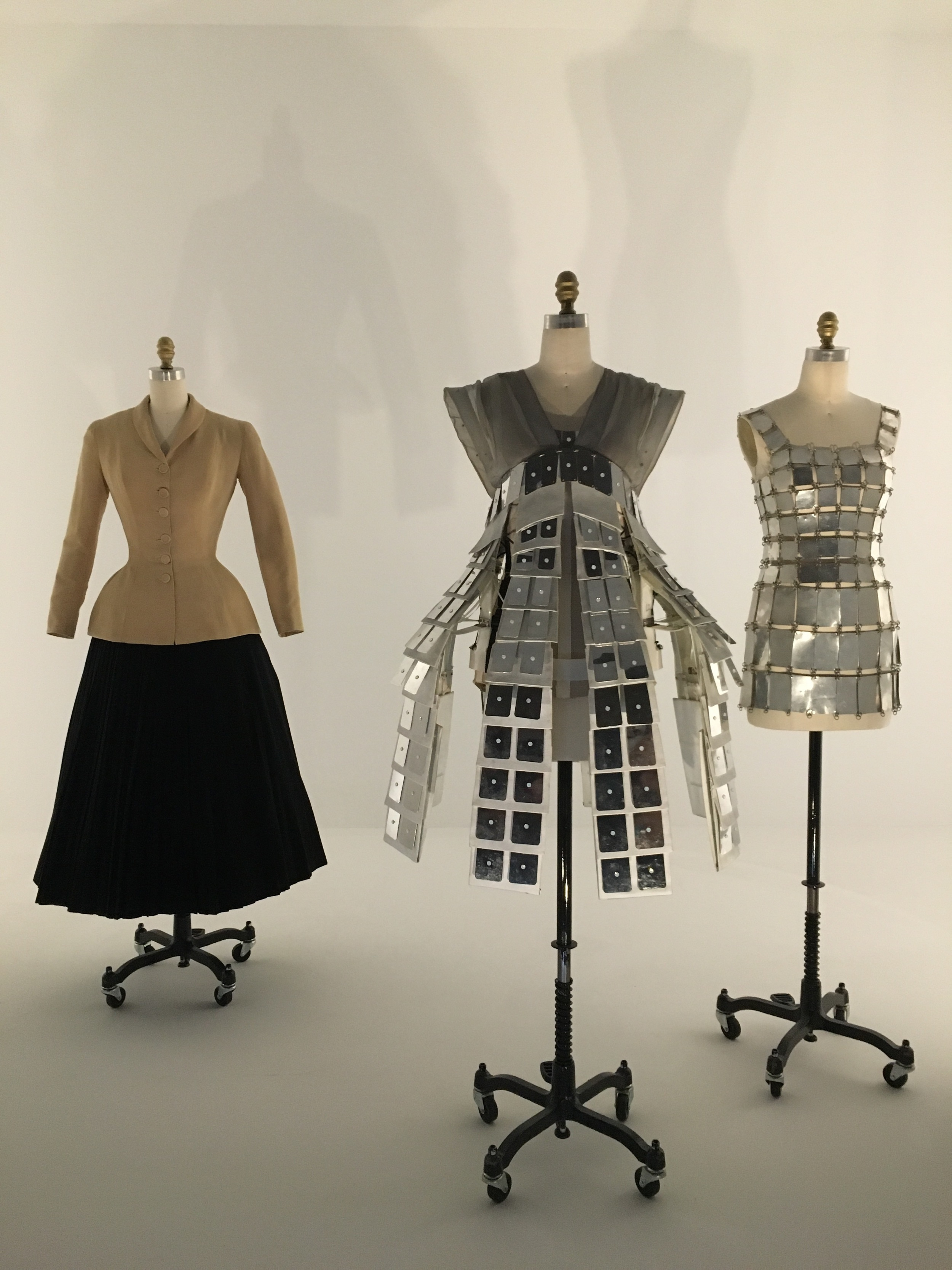 House of Dior  Christian Dior  SS 1947, haute couture  Machine-sewn beige tussah silk plain weave, hand-stitched bound buttonholes, hand-pad-stitched interlining    Hussein Chalayan  SS 2007,prêt-à-porter  Machine-sewn gray silk organza bodice; machine-sewn gray cotton-synthetic sateen tabs; aluminum plaques with hand glued Swarovski crystals; machine-molded plastic understructure, machine-sewn boned foundation threaded with monofilament wire, pulleys, and electronically controlled, geared motor components    Paco Rabanne  1967, haute couture  Machine-cut silver aluminum, hand-punched and linked with silver metal jump rings