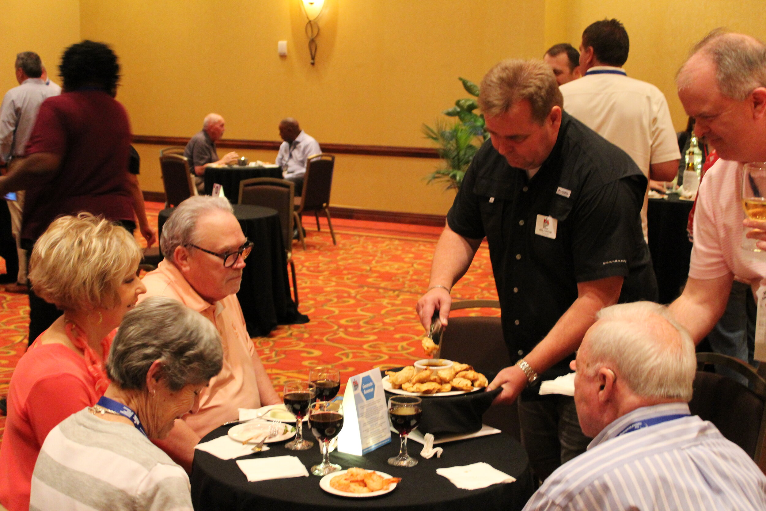 Greg Augustine showing his serving skills at the Welcome Reception.JPG
