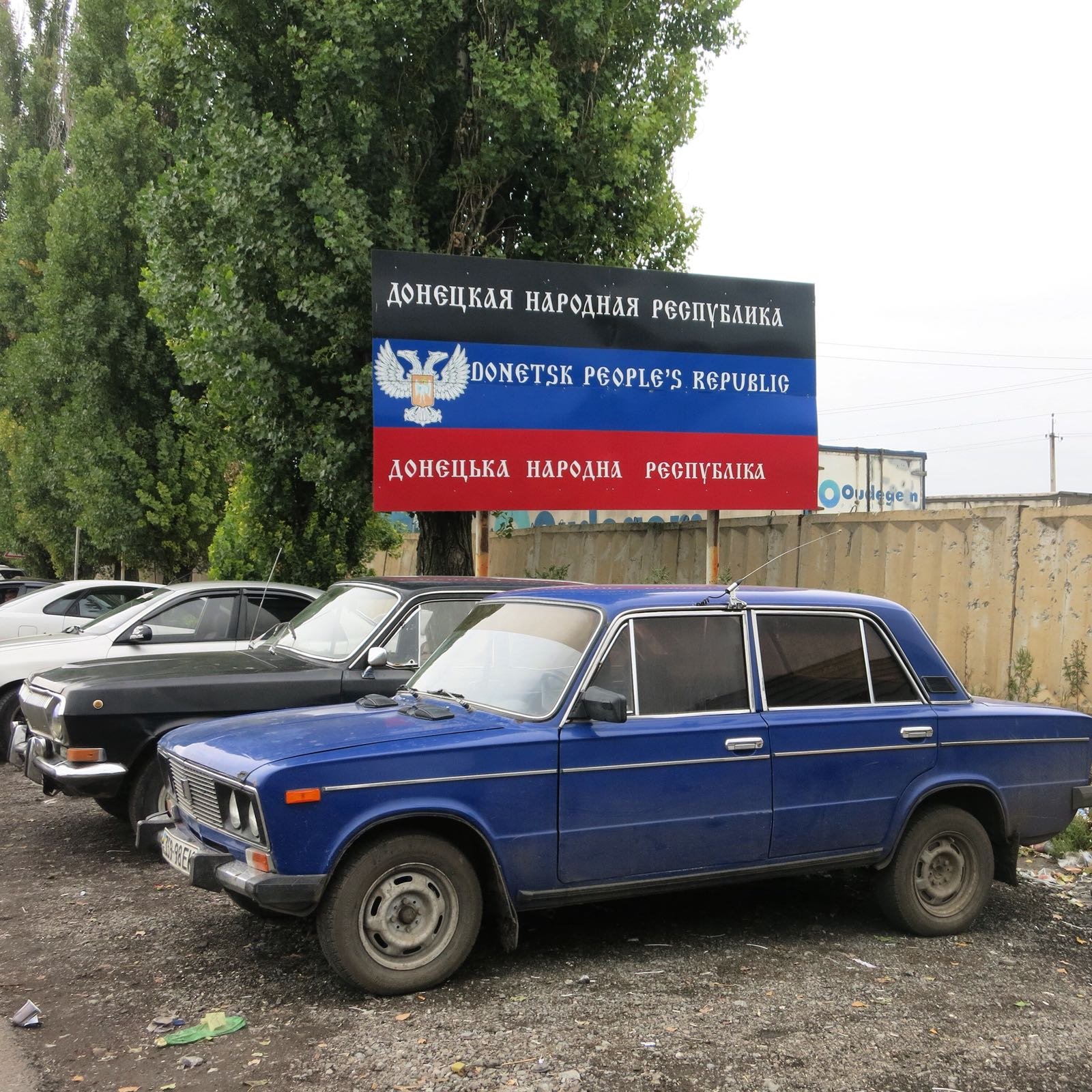 """A blue Lada and (what I think is) a black Volga conveniently located at the border crossing into the new """"People's Republic of Donetsk""""."""