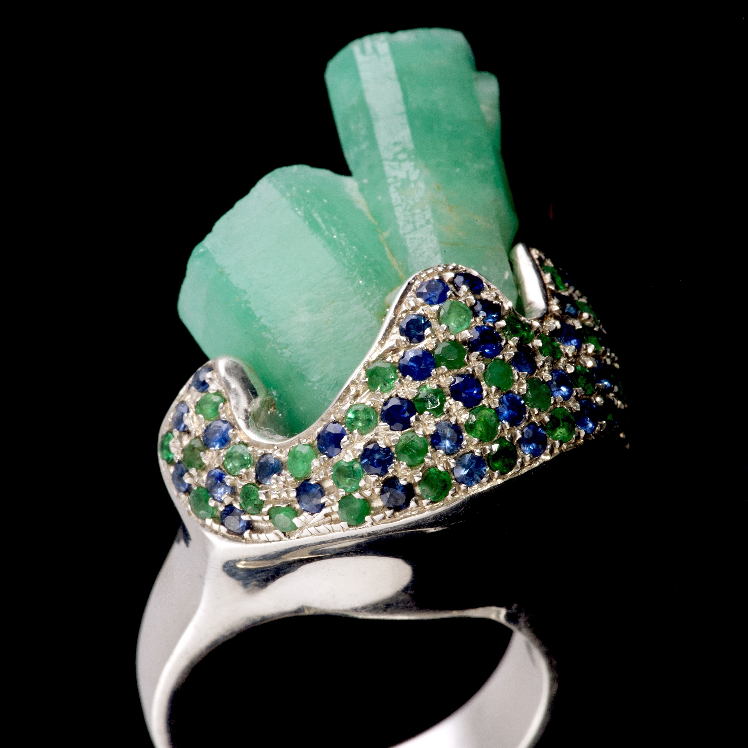 A  macle  or unique double rough emerald crystals are embraced by sapphire and emerald pavé. Ring is set in 925 silver
