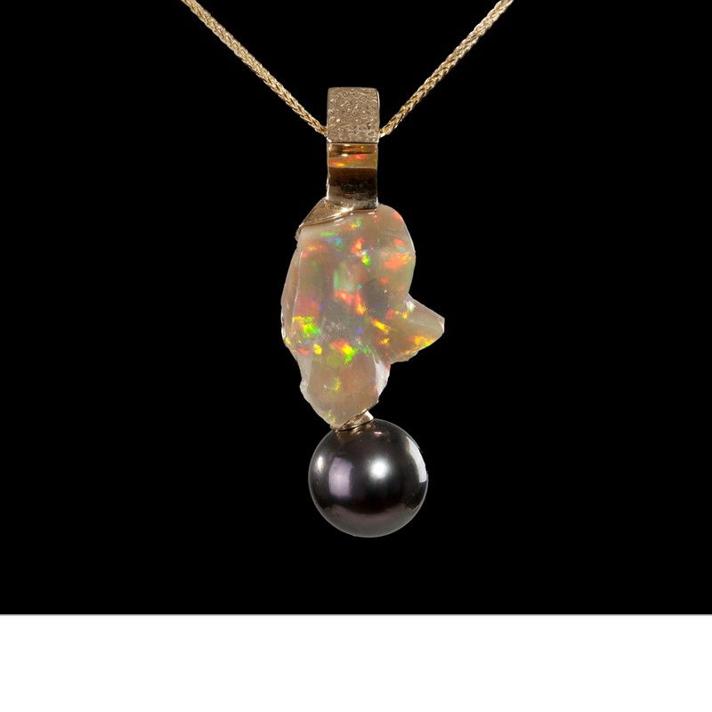 A Tahitian pearl (14mm) dangles from a Wallo (Ethiopia) opal. Capped by an 18K gold clasp and suspended from a gold chain