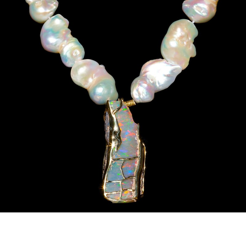 A magnificent 300 cts of Wallo (Ethiopia) opal are outlined in 18K gold and suspended from a necklace of Chinese freshwater pearls