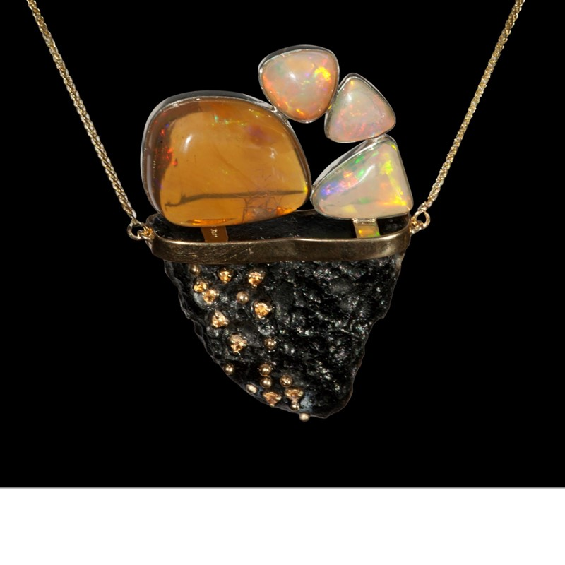 On a swing of Chinese tektite balances a large crescent fire opal from Ethiopia and 3 Ethiopian Wallo opals, with yellow sapphire pavé