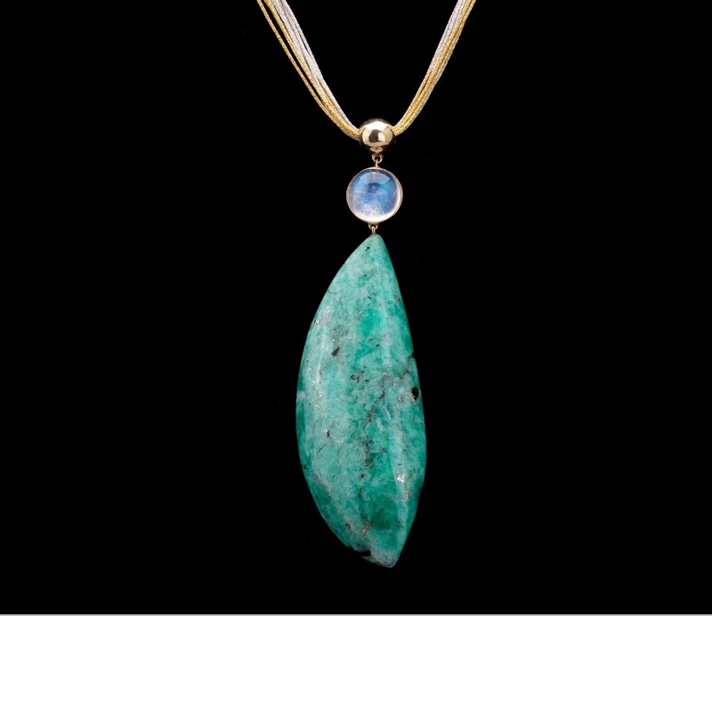 A rough emerald half moon (193 carats) from Colombia impressively grabs the stage, hanging from a round blue moonstone (4.5 carats) and a golden bead. Set in 18K gold, suspended from entwined silver and gold silk ribbons.