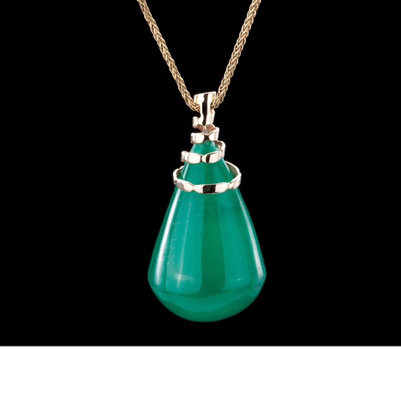 A perfect pear of just over 60 carats emerald. Captured in a 18 gold spiral and hung from a gold chain