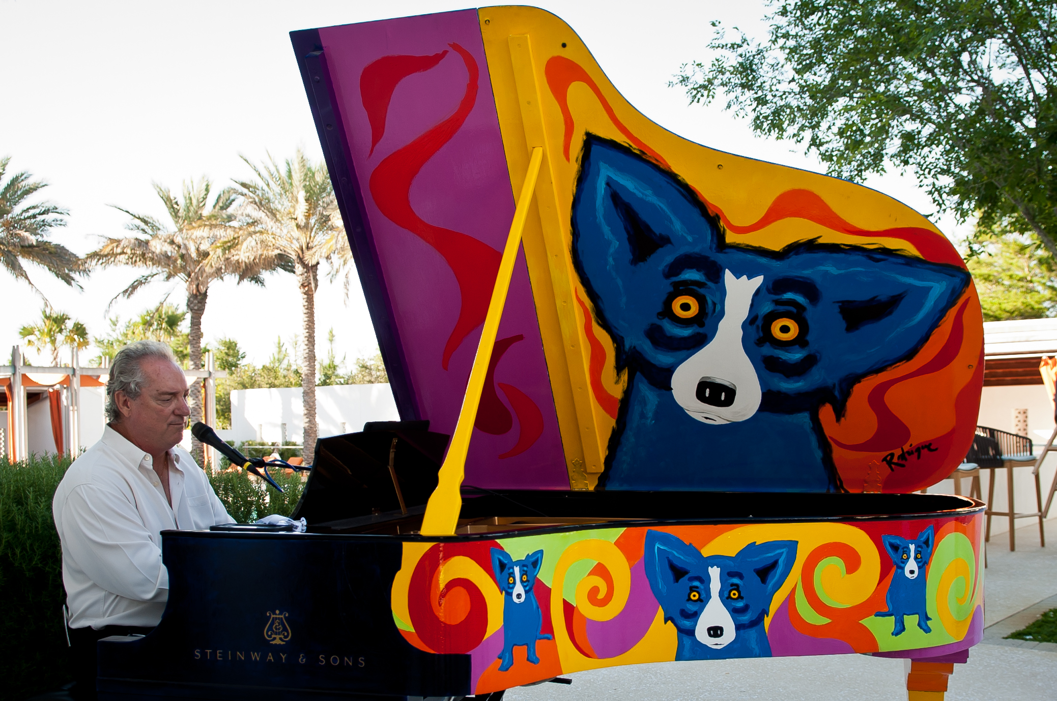 - David Seering entertains guests at The George Rodrigue Steinway event following unveiling of the Rodrigue sculpture on opening night.