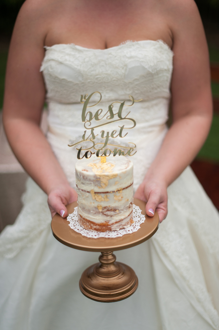 Love this!! Bride holding a mini wedding cake on small simple gold cake stand
