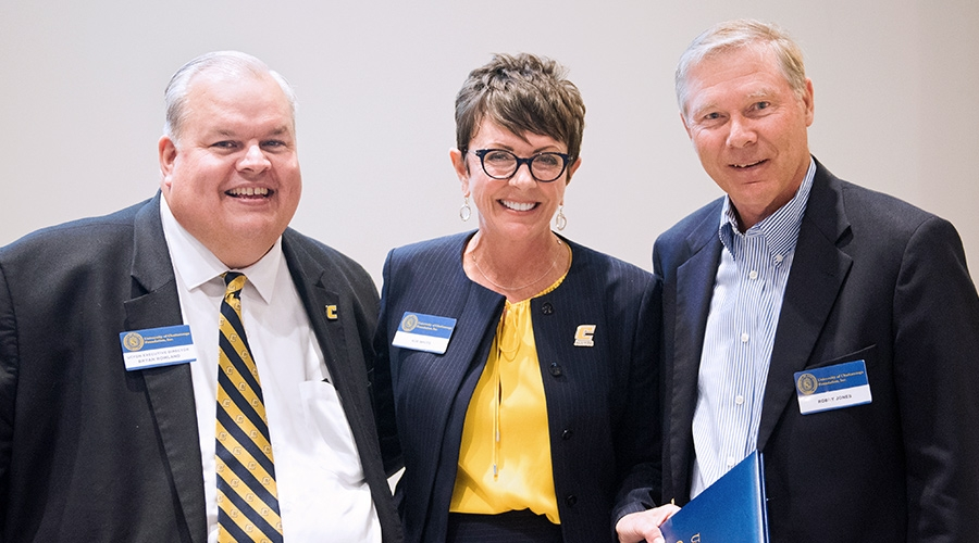 Vice Chancellor Bryan Rowland and UC Foundation Board Chairperson Kim White present outgoing trustee Robby Jones with a certificate recognizing his eight years of service to the board.