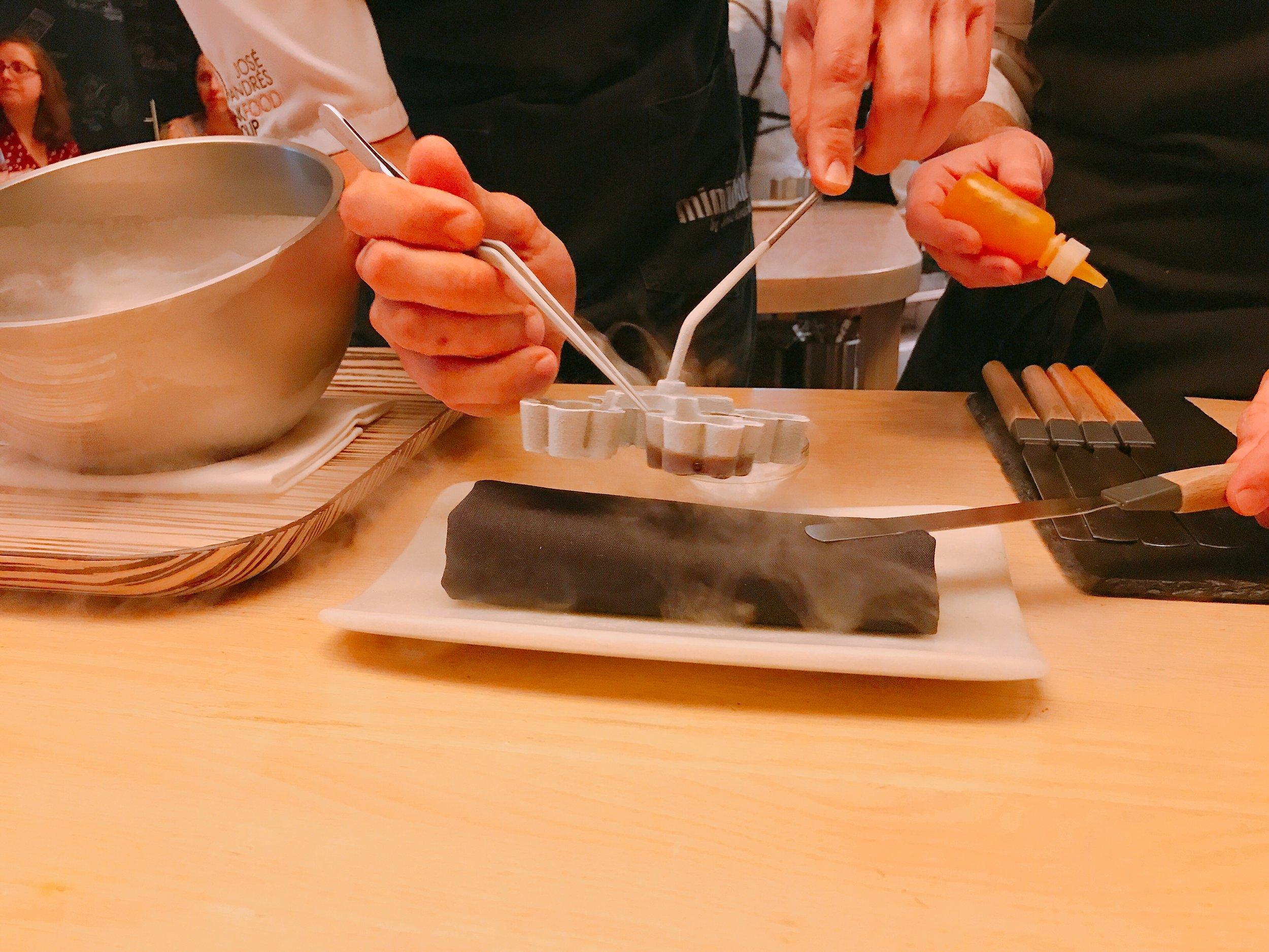 The culinary team crafting the pumpkin oil tart using liquid nitrogen