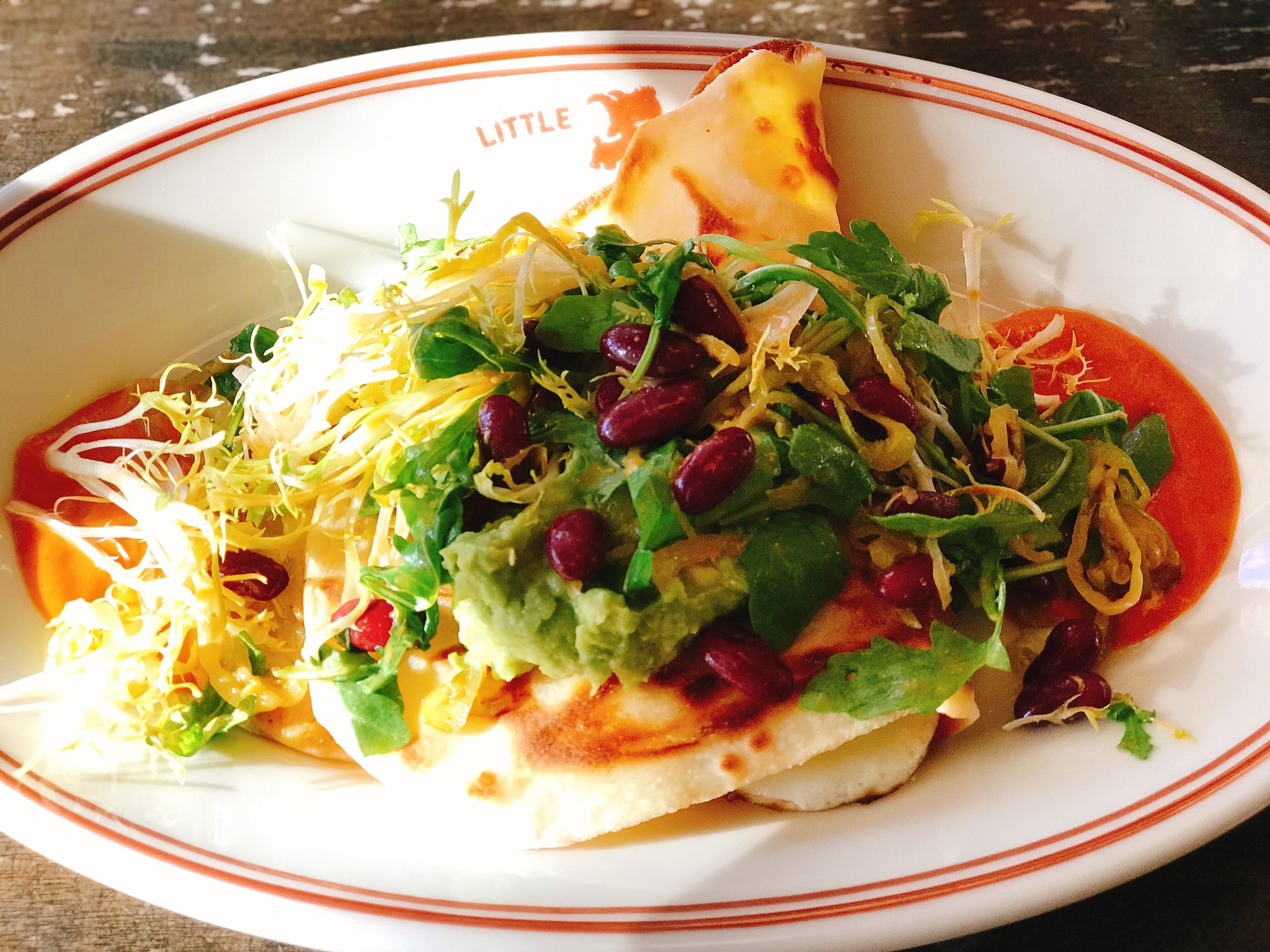 Parathas Burrito: Indian flatbread, chili pepper sauce, avocado-bean salad, sunny side eggs and mont amore cheese