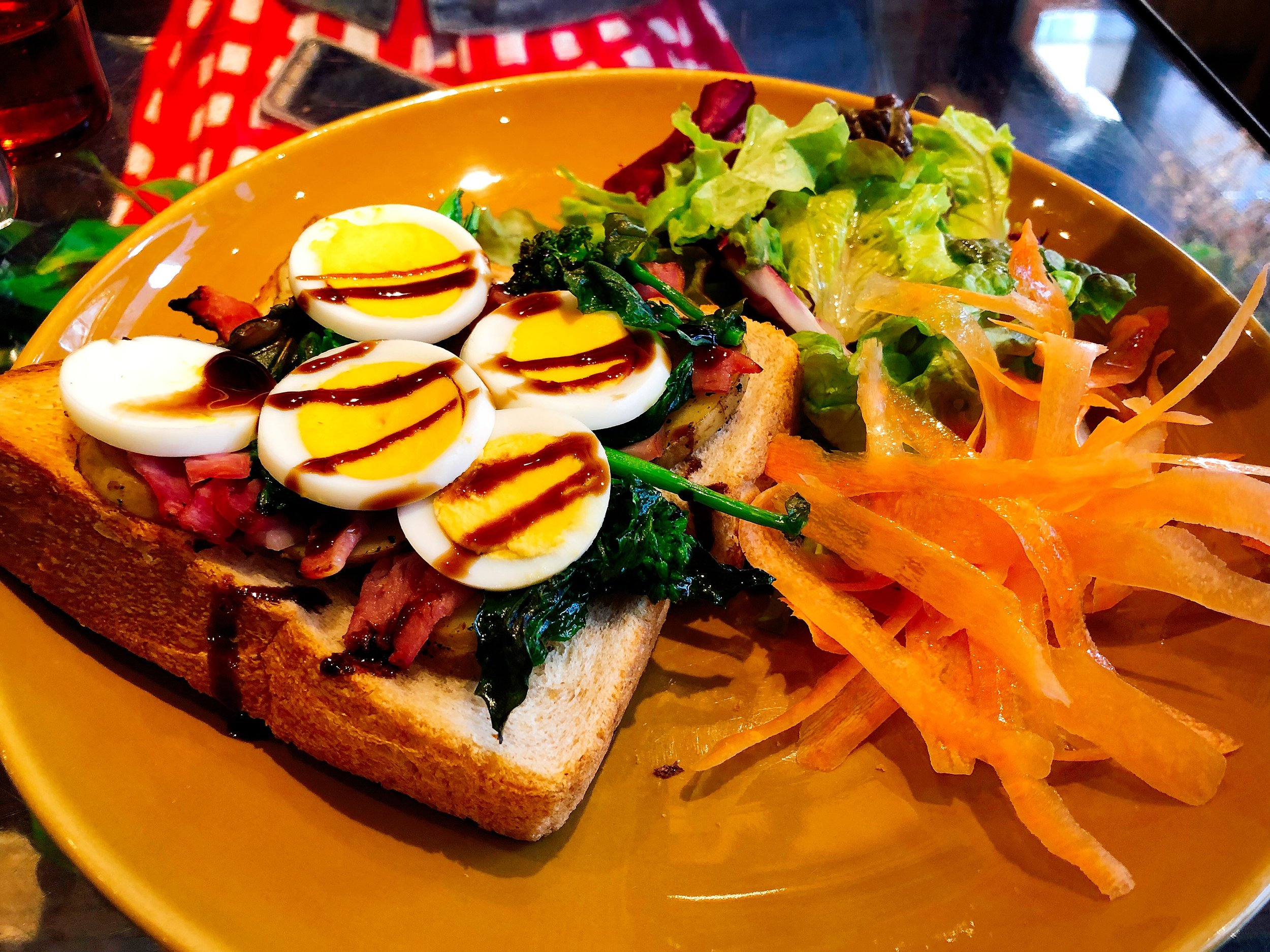 Toast Topped With Ham, Egg Broccolini And A Drizzle Of Balsamic Vinegar