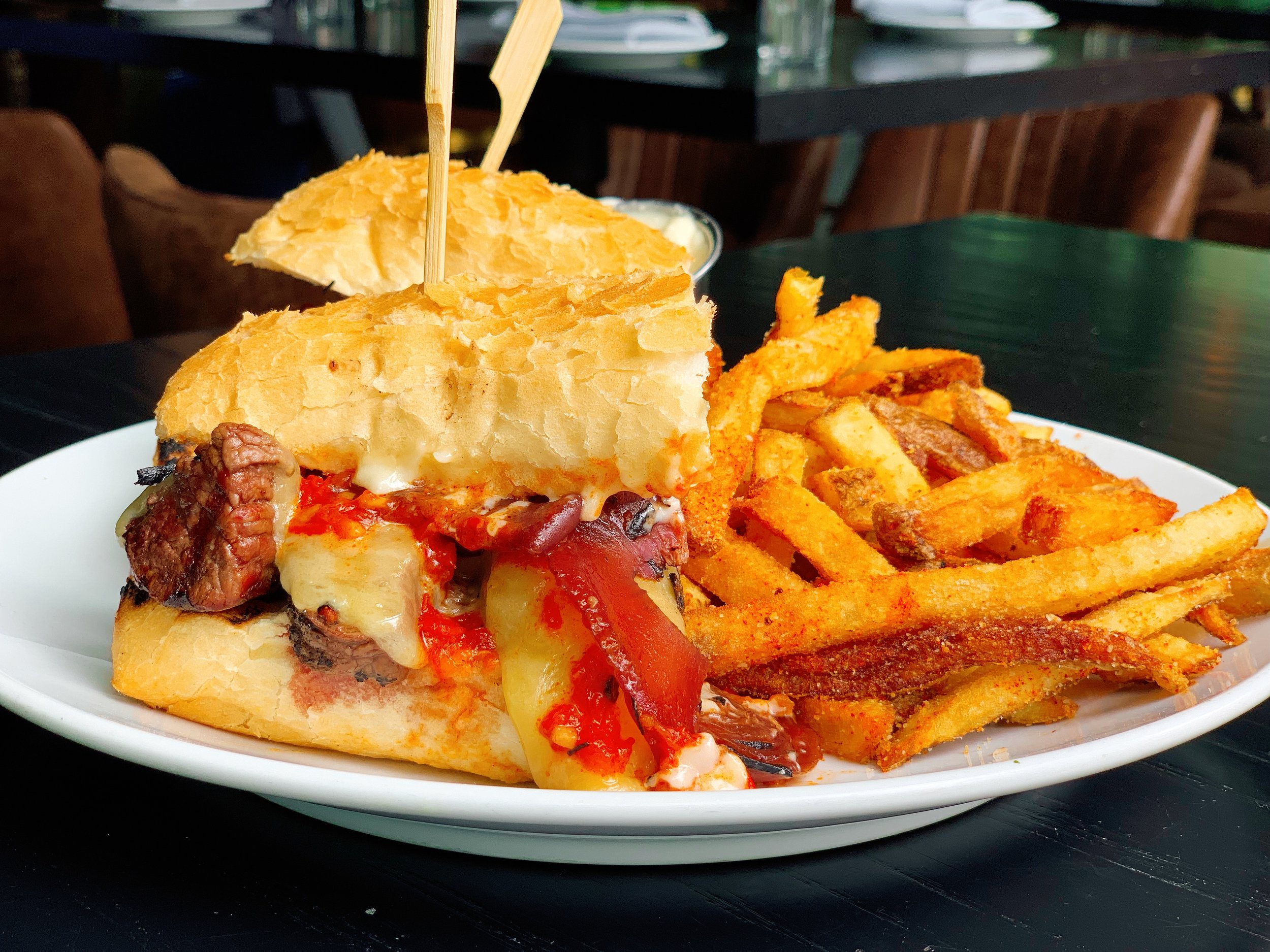 Grilled Top Sirloin Sandwich Served With Housemade Fries And Parmesan Aioli | Red Wine Onions + Harissa Sauce + Roasted Garlic Aioli + Aged White Cheddar Cheese + French Roll