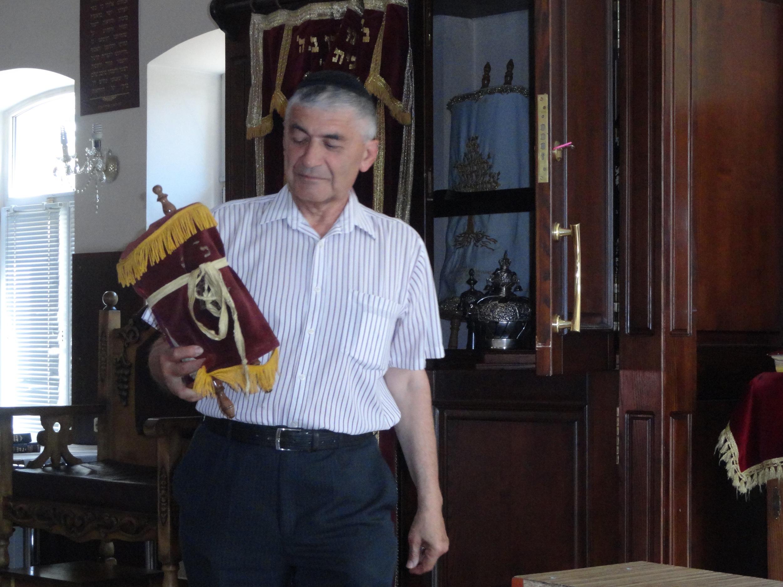 Joseph Liberman holding a torah that survived the Holocaust in Pinsk, Belarus.