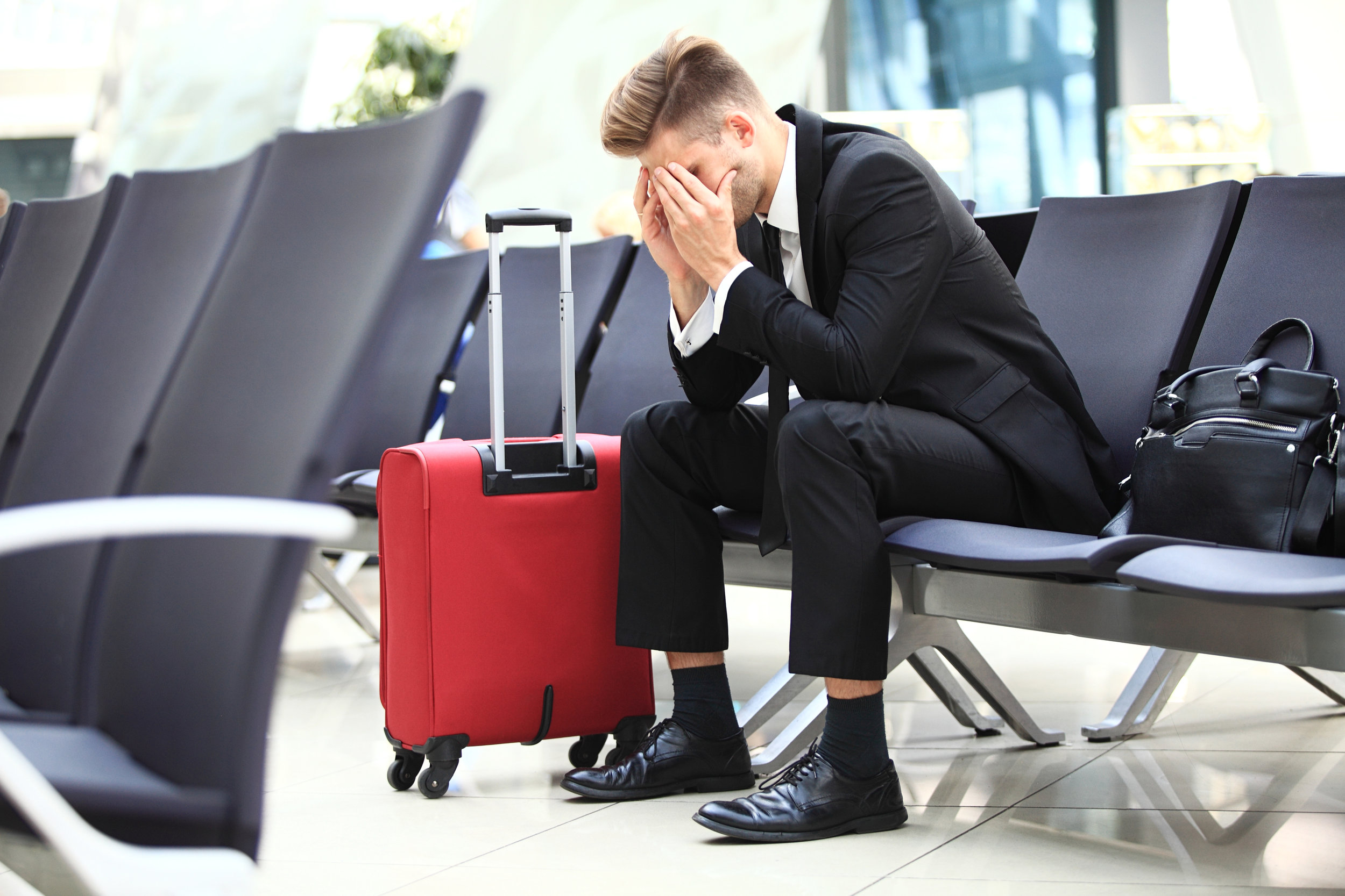 frustrated_business_traveler_at_the_airport_sanctifly_travel_wellness_app.jpeg