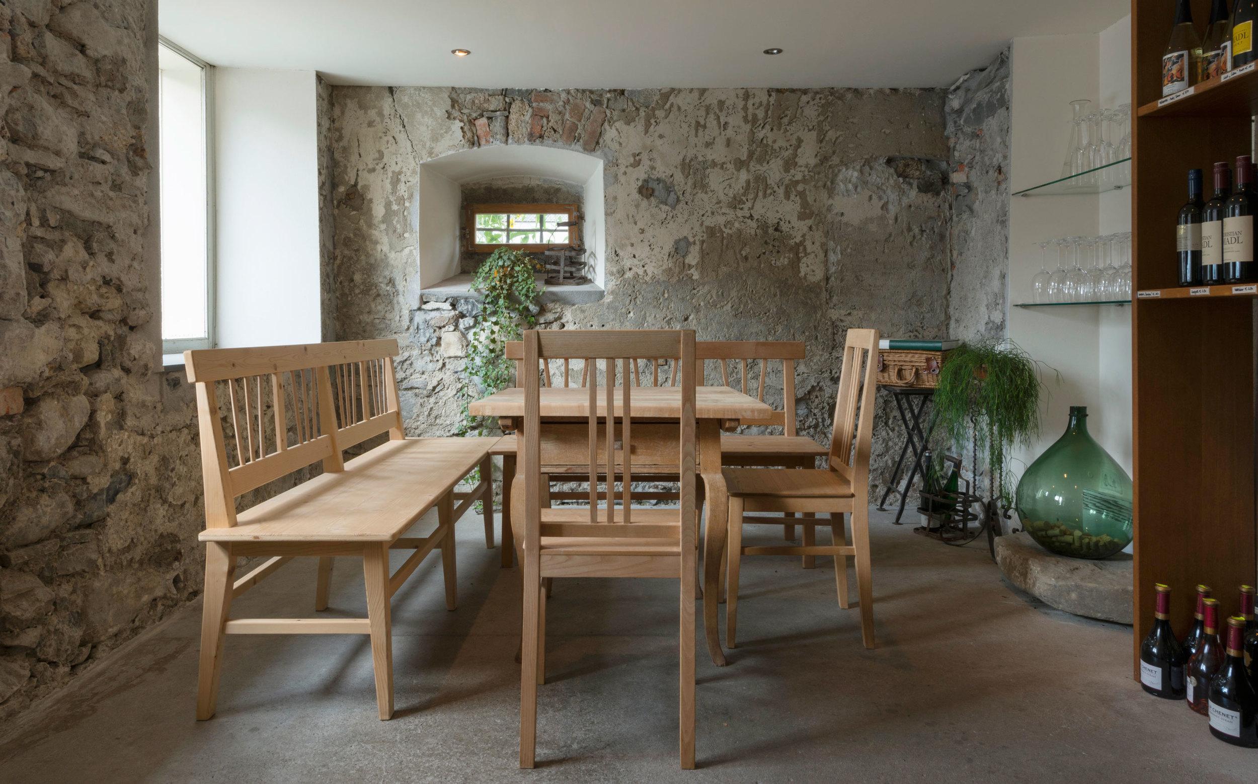 Blick vom Gang in den Weinkeller hinein. In der Mitte steht ein Holztisch mit zwei Bänken und zwei Stühlen die von Florian Berchtold – Hedis Ehemann – selbst gebaut wurden.