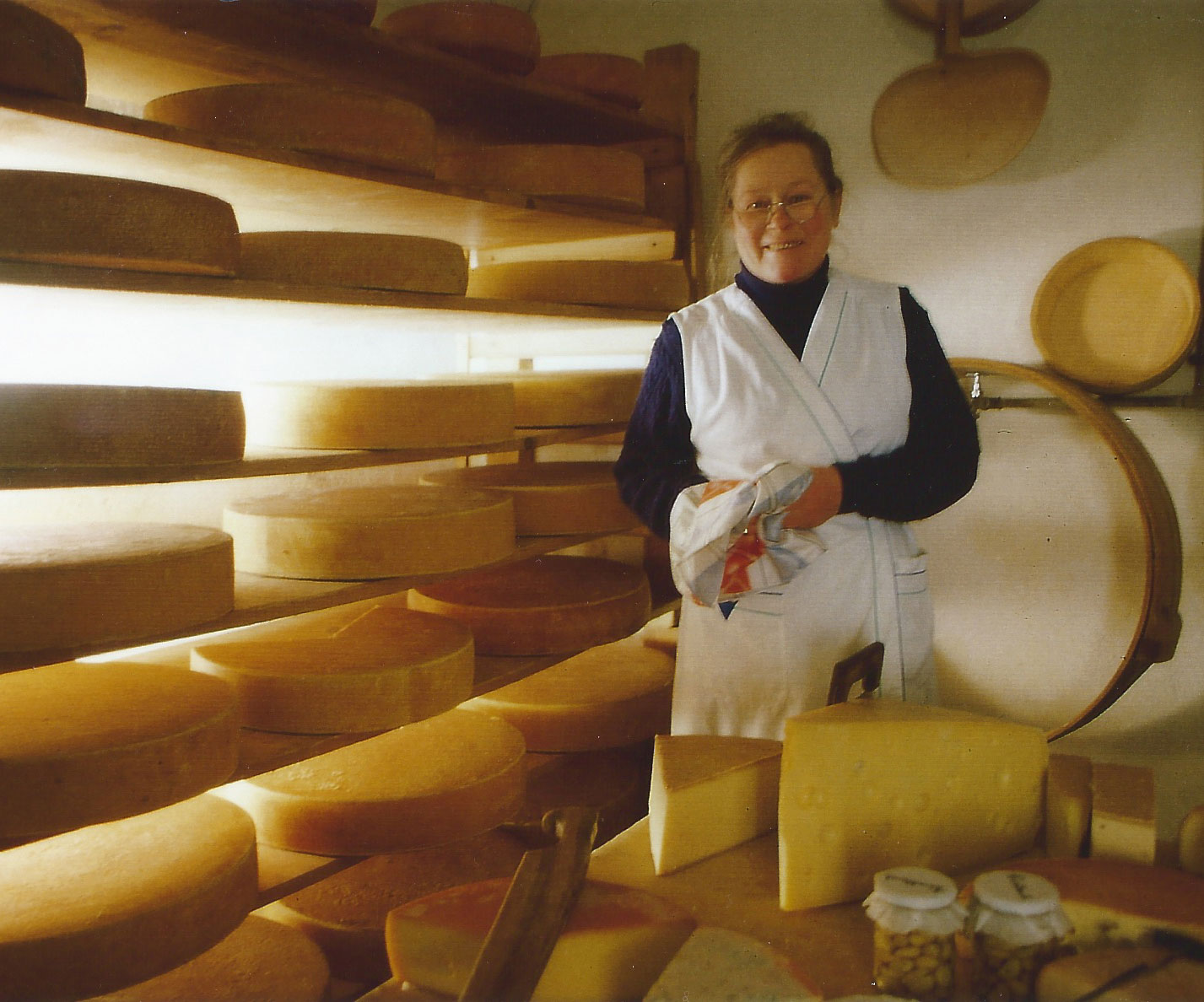 Maria steht mit einem großen Grinsen im Gesicht im Käsekeller, die Brille etwas runter auf die Nase gerutscht, wie man sie kennt.Hinter ihr stapeln sich die Käselaibe im Regal. Vor ihr ein riesiges Stück Emmentaler und verschiedene andere Käsesorten.