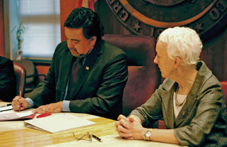Representative Gail Chasey , looking on as Governor Richardson signs the bill repealing the death penalty.