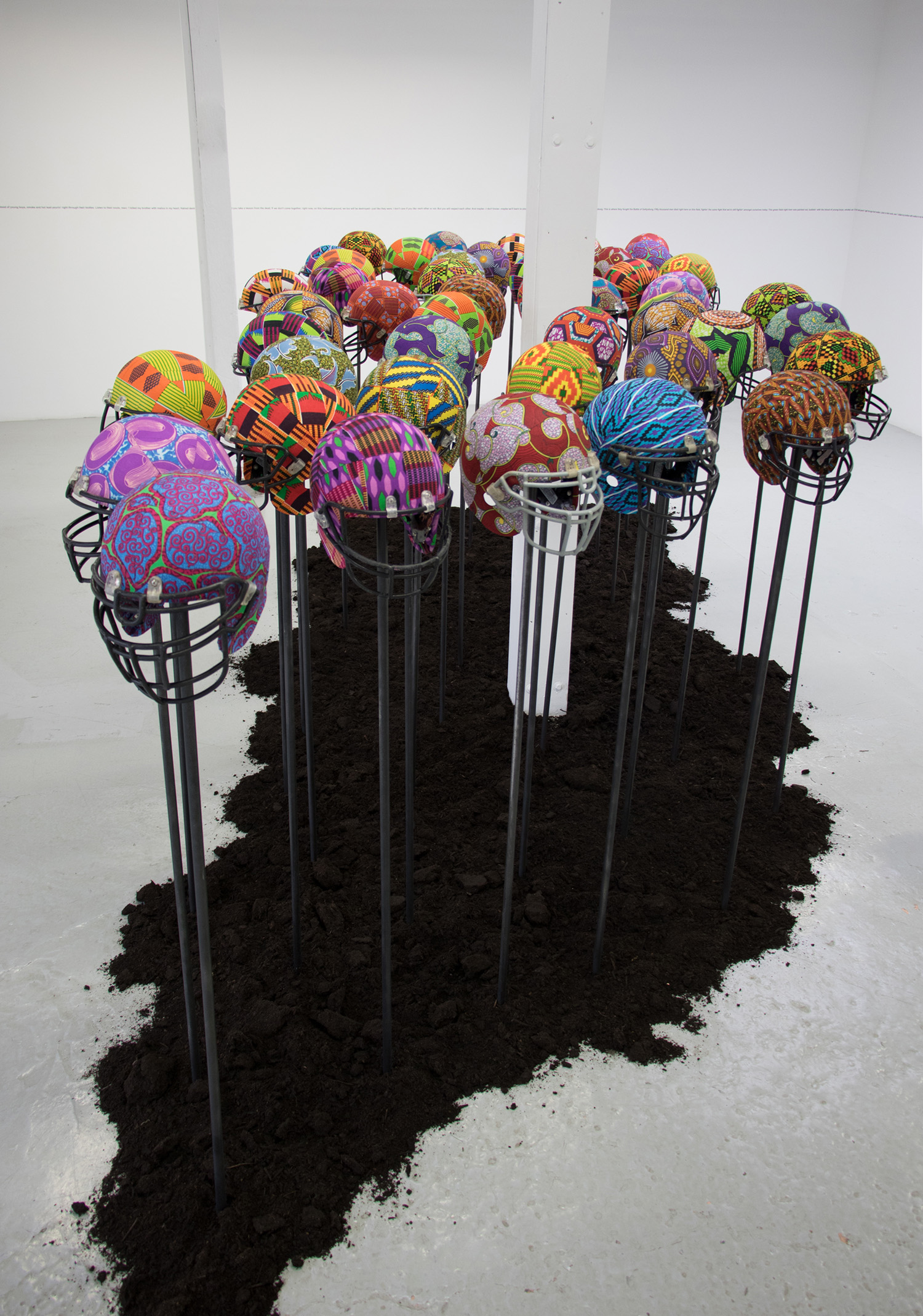 Glorious Bones , 2018, installation of 46 , used football helmets, African wax print textile, adhesive, steel stands, earth