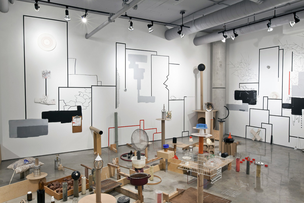 ALLUVIA , 2012, cardboard, tempered found and ready-made objects, drawings and paint on paper, wood and on walls, masking tape, installation view
