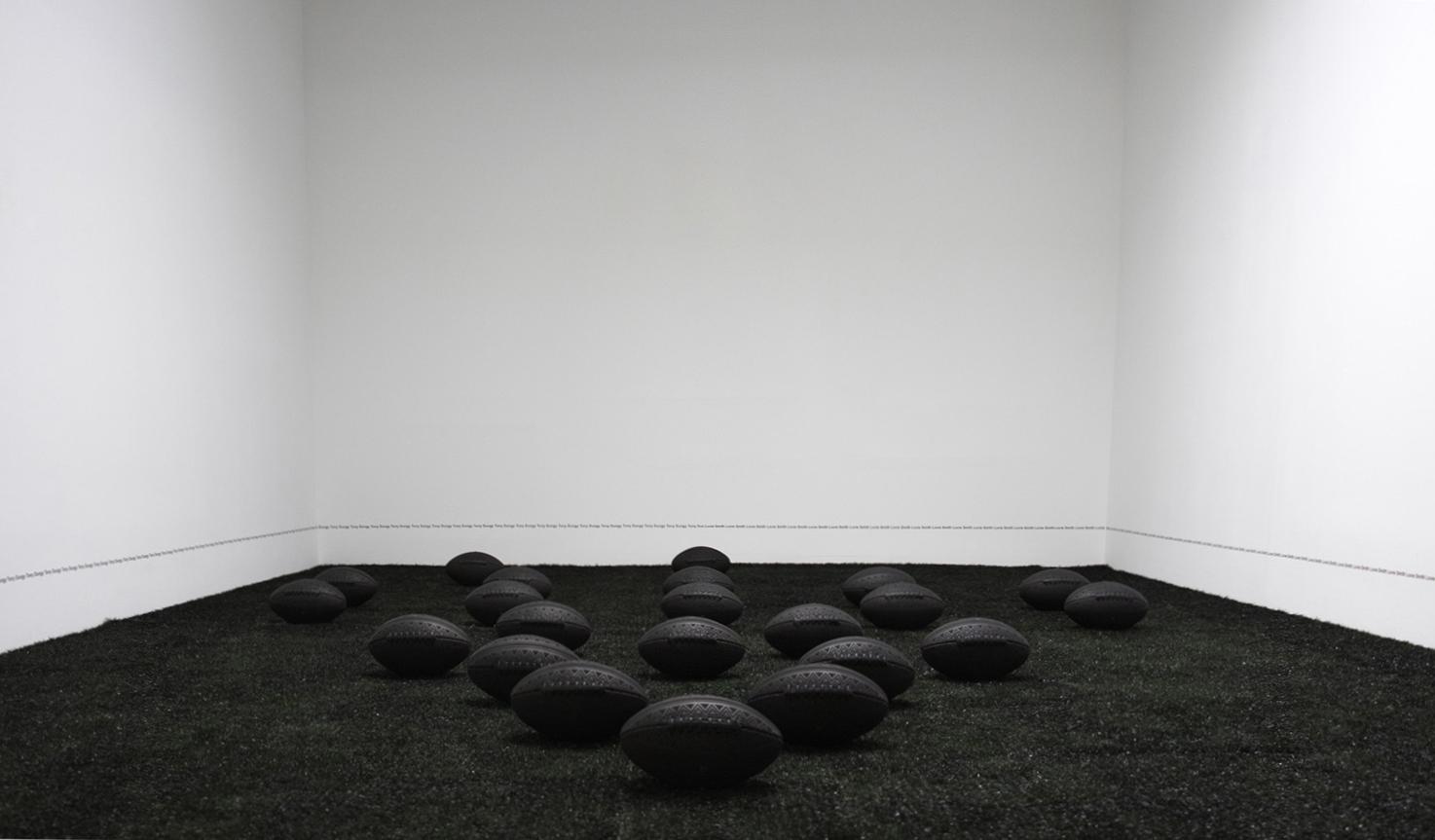 Blood and Tears Instead of Milk and Honey , 2018, 22 black leather braded footballs on black astroturf