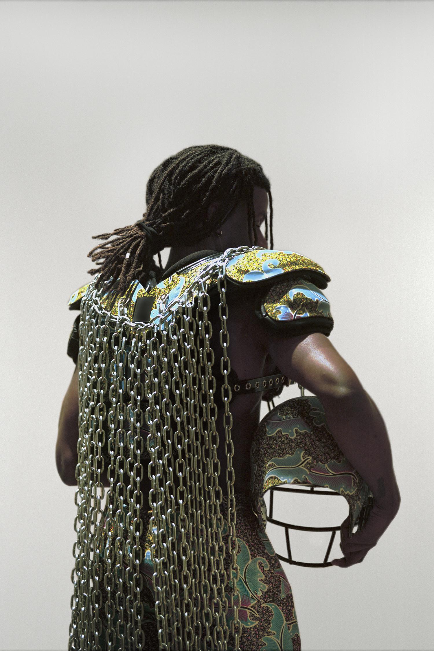 Untitled (No Fields) , 2018, repurposed football gear, African wax print, chain, black astroturf, Nikes