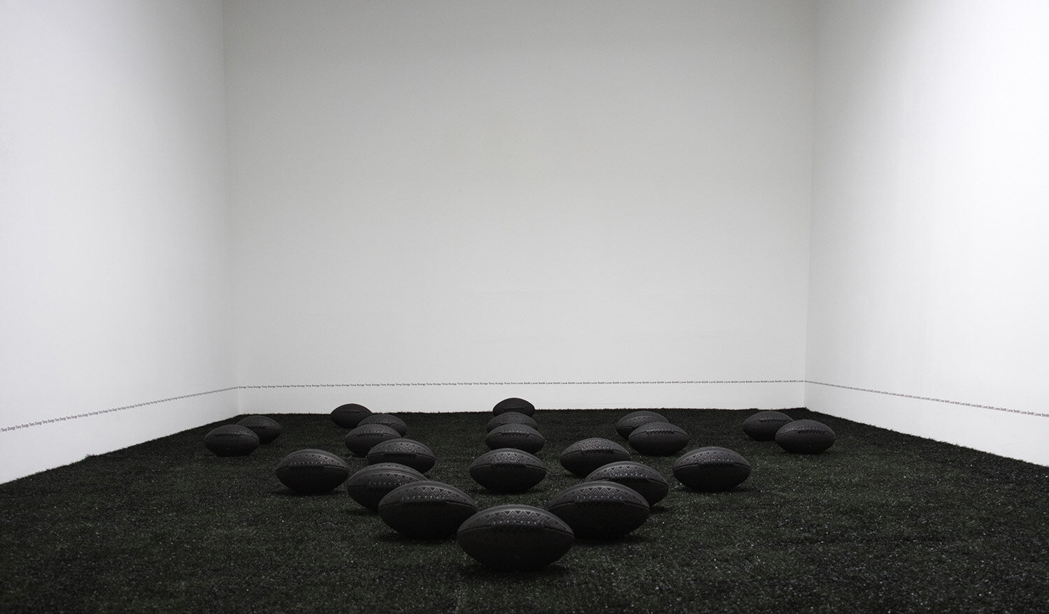 Blood and Tears Instead of Milk and Honey,  2018, installation of 22, custom-made leather footballs, synthetic turf, spray paint, ceramics