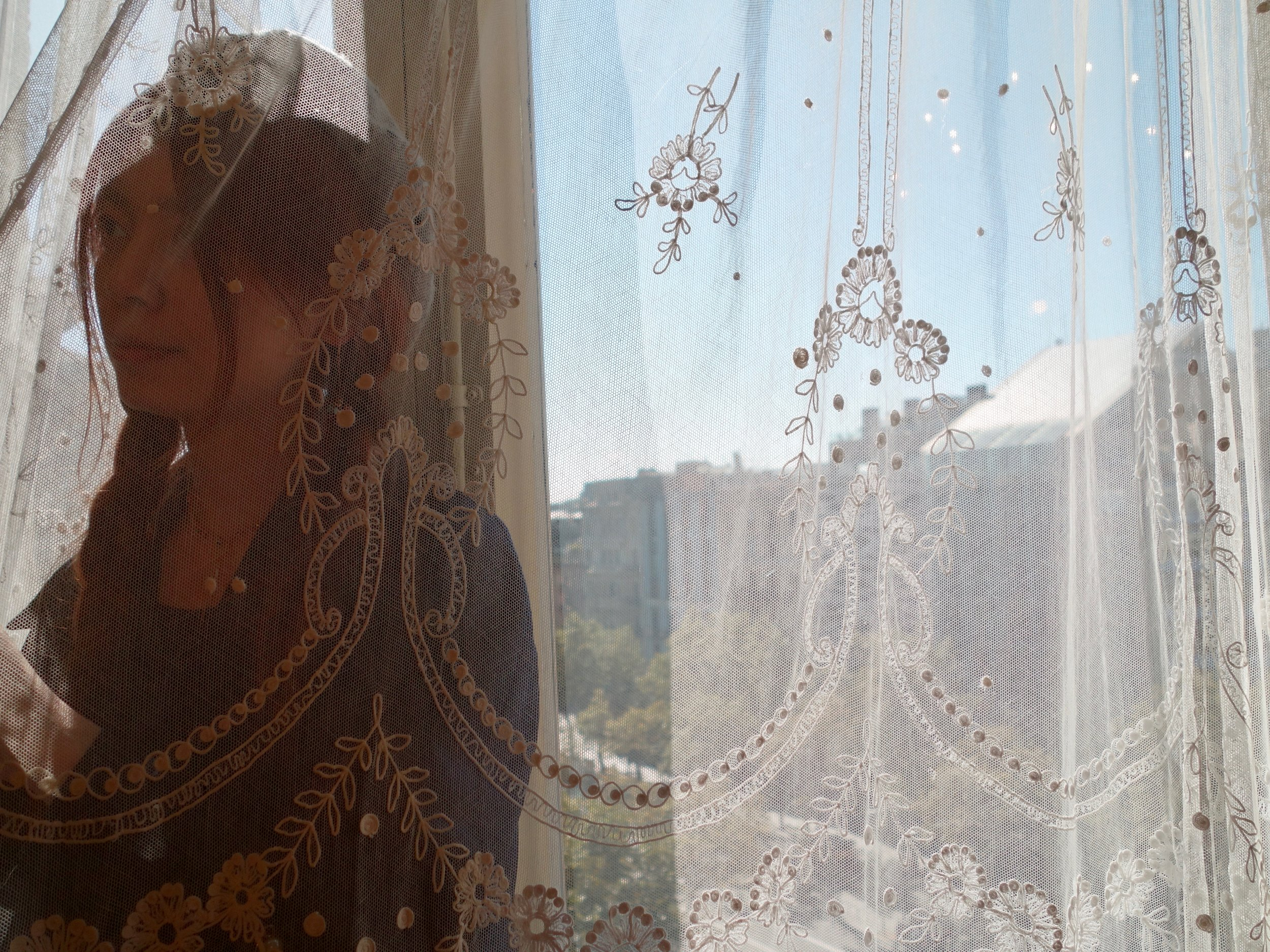 Woman Behind Lace Curtain in Gaudi Apartment.jpg