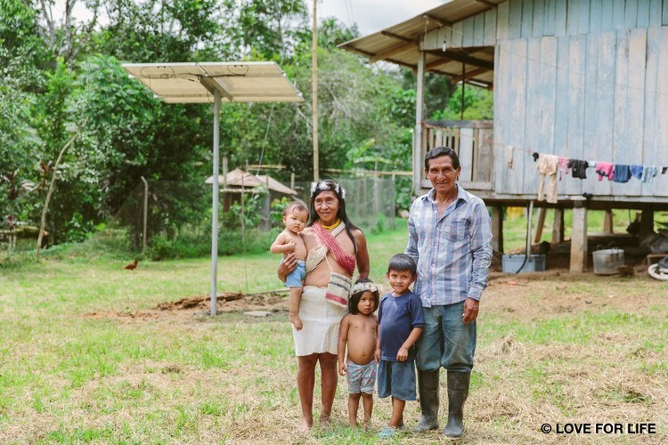 A Waorani family in front of their newly installed solar system, which provides electricity for the first time in the Amazon. It not only allows light, but also an independent and self-determined life.