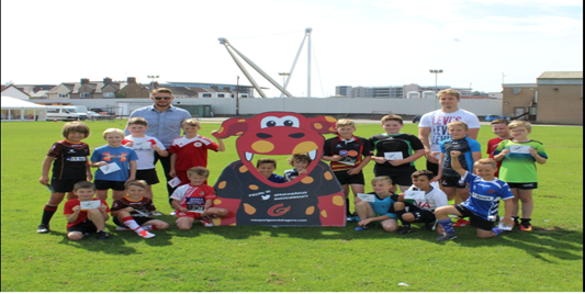 Wales international Tyler Morgan and Dragons captain Lewis Evans with participants of the Dragons Summer Skills Camp
