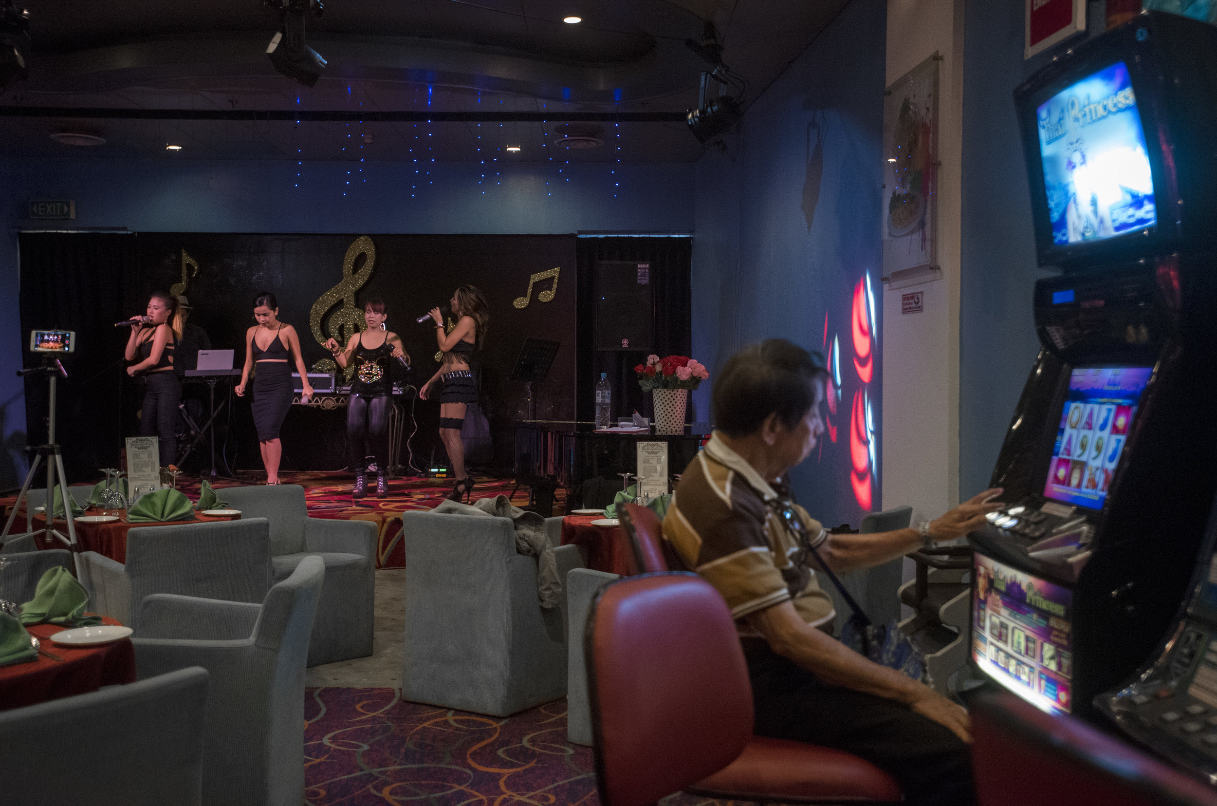 A group of female singers perform in the bistro as a man tries his luck at a jackpot machine on board the M/V Amusement World, March 15, 2018.