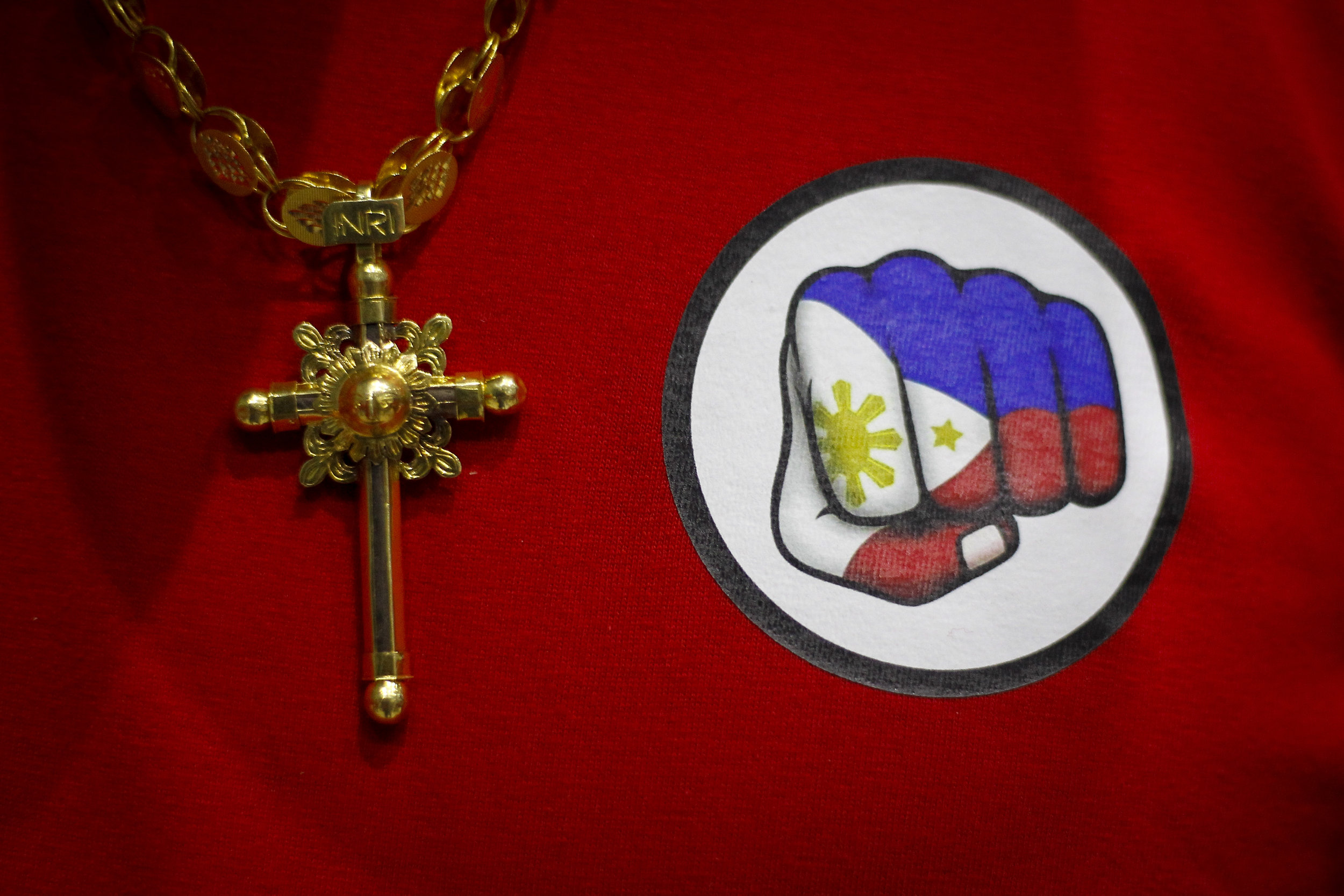 A crucifix is pictured next to Philippines President RodrigoDuterte's campaign logo on a t-shirt worn by a supporter in Singapore, April 28, 2018. REUTERS/FelineLim