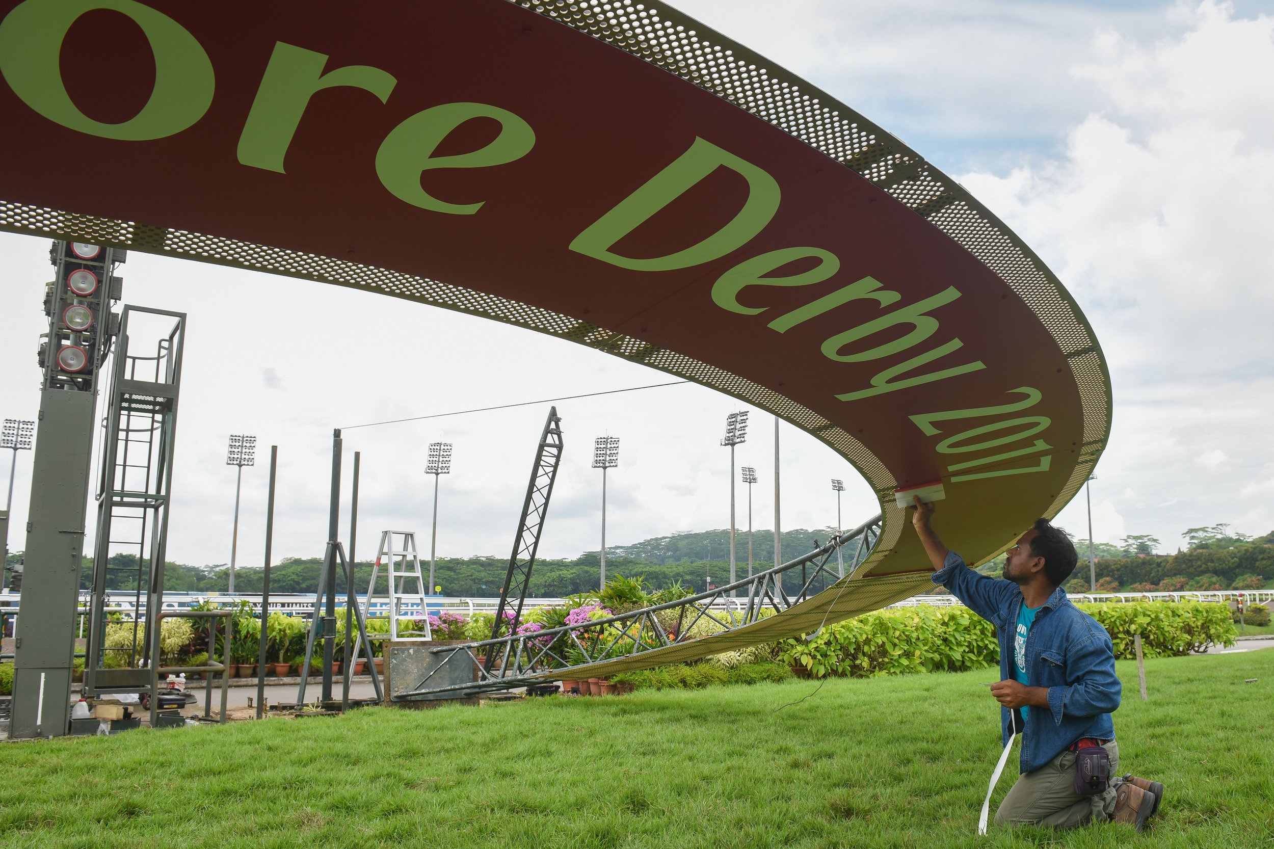 A worker putting the finishing touches to the Emirates Singapore Derby banner, which is shaped like a horseshoe, on Saturday, the day before the race. As live races are held on Fridays and Sundays, Saturdays can get busy as workers have to tear down the decorations for the previous day and put up new ones.