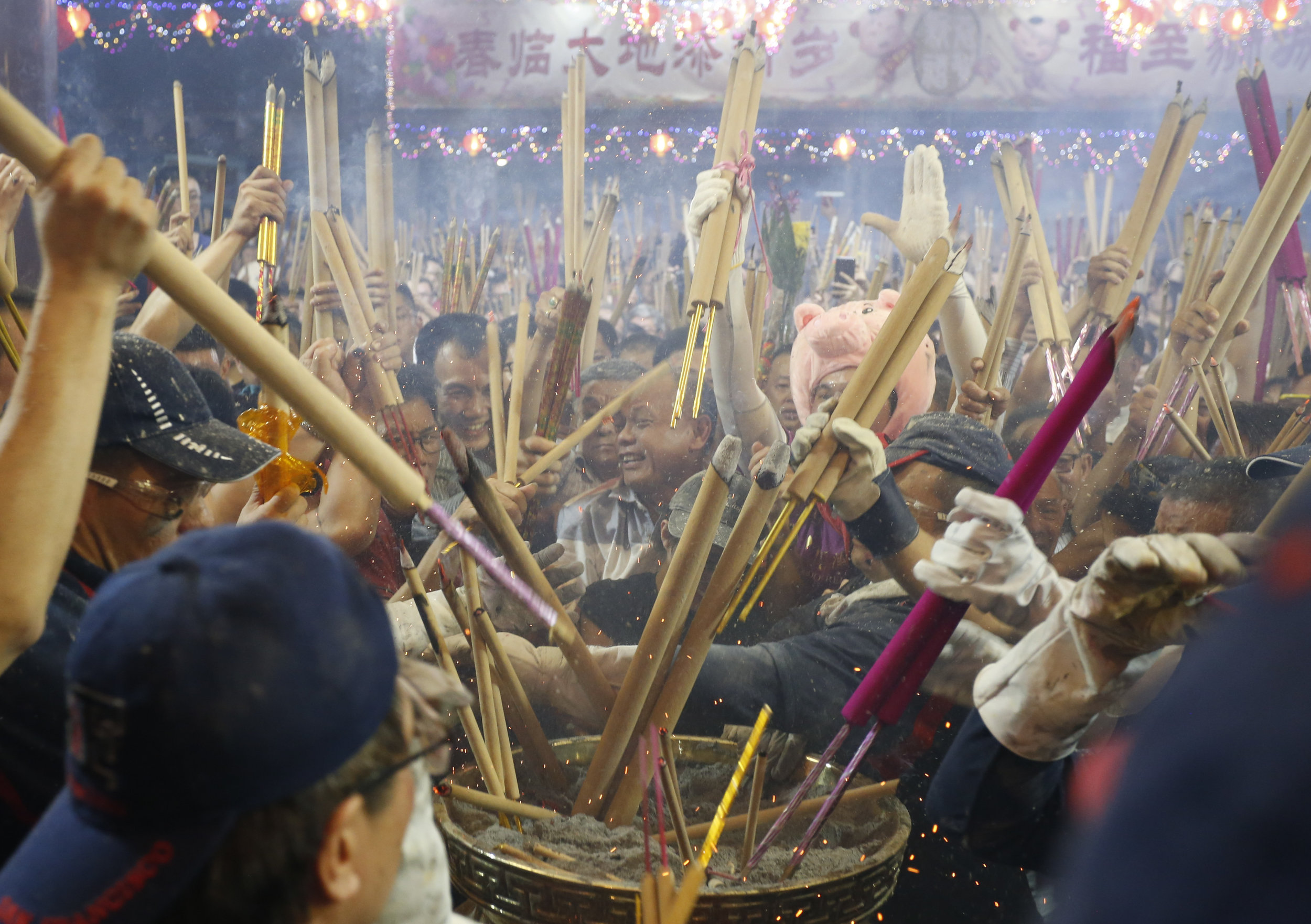 People rush to plant the first joss stick of the Lunar New Year of the Pig at the stroke of midnight at the Kwan Im Thong Hood Cho temple in Singapore, February 4, 2019. REUTERS/Feline Lim