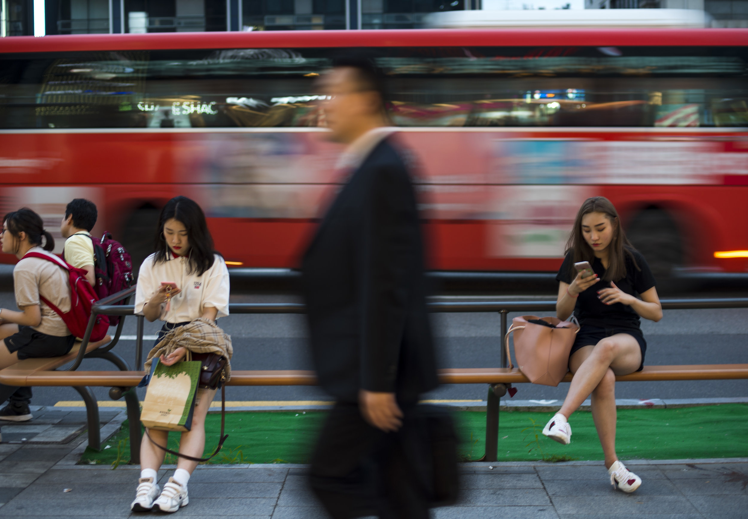 People use their mobile phones on a busy street in Seoul, South Korea. With falling birth rates and rising divorce rates, South Korea is seeing an uptick in businesses focussing on solo consumers. This has had a ripple effect, with more people embracing time spent alone.