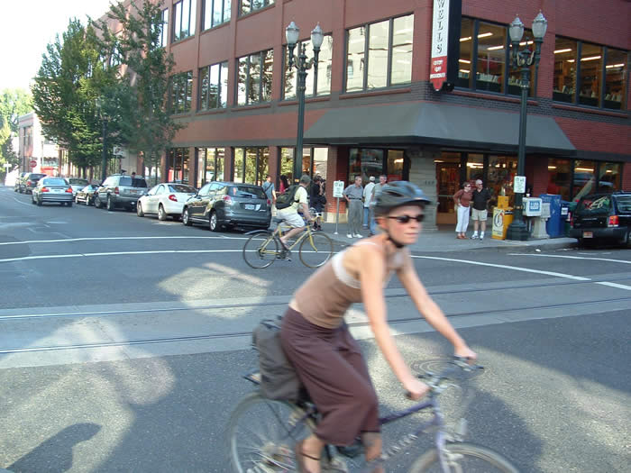 Streetcar tracks and bicyclists travel by  Powell's Books.