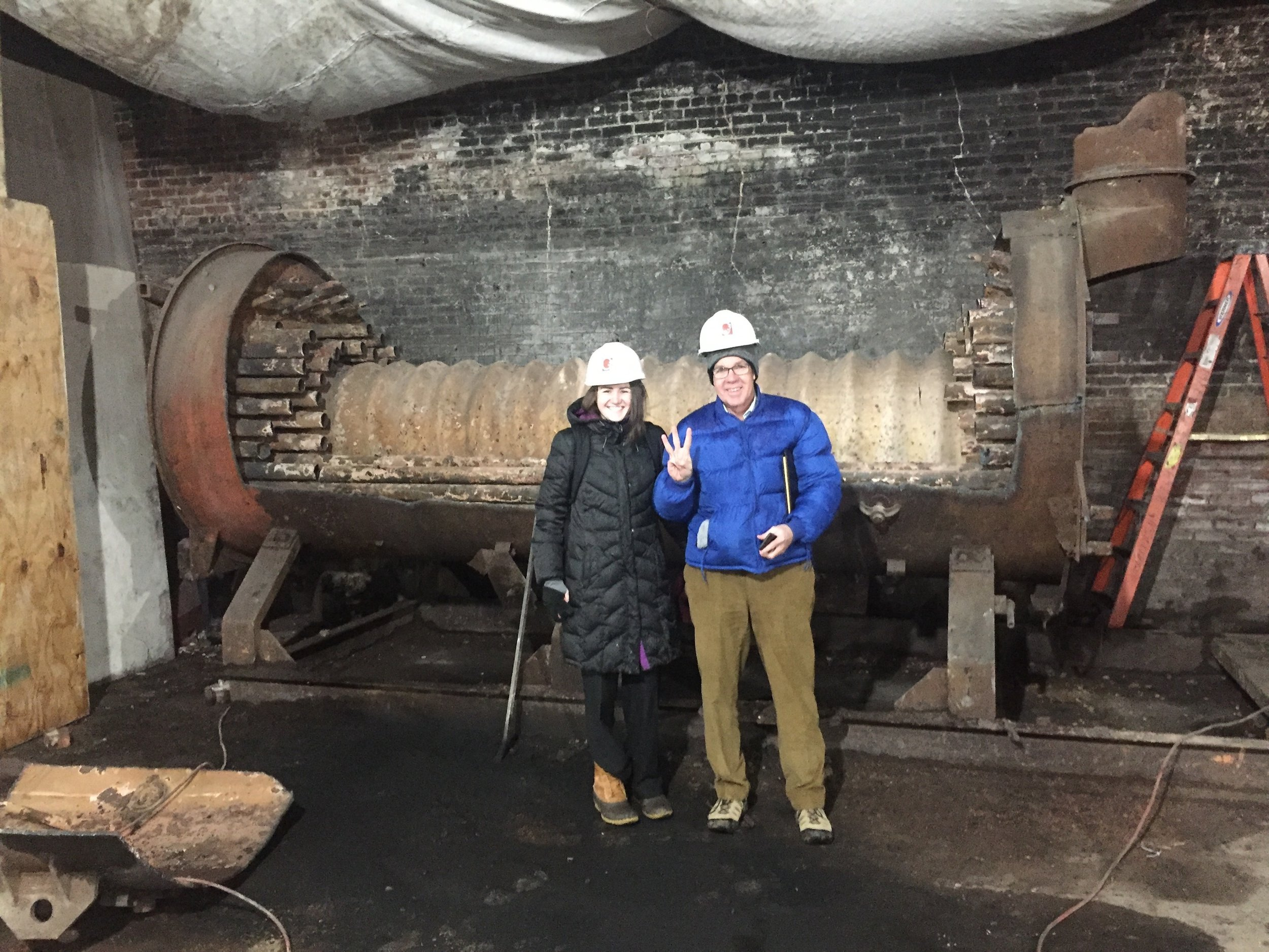 John McConnell, Founder and President, and Tara Hank, Development Office Coordinator, stand in front of the old boiler.