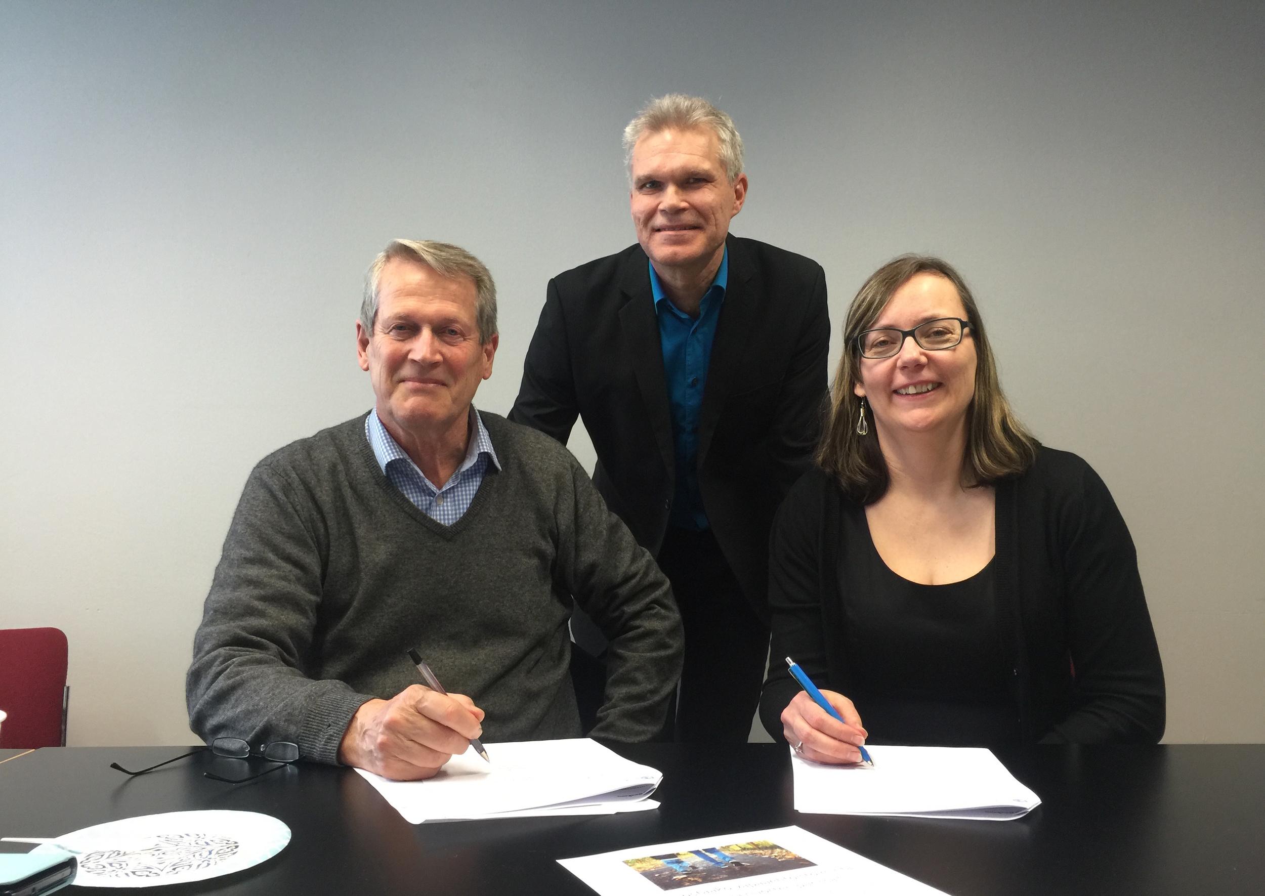Sanna Airaksinen (oik.) ja Antti Perttu allekirjoittavat yhteistyösopimusta. Taustalla Pekka Puukko.