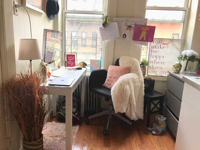 """Ashleys desk - 27 inch iMac, gold mouse pad, easter egg note holders, gold unicorn lamp, marble clock, bedazzled mouse & a framed photo that says """"You Got This""""."""