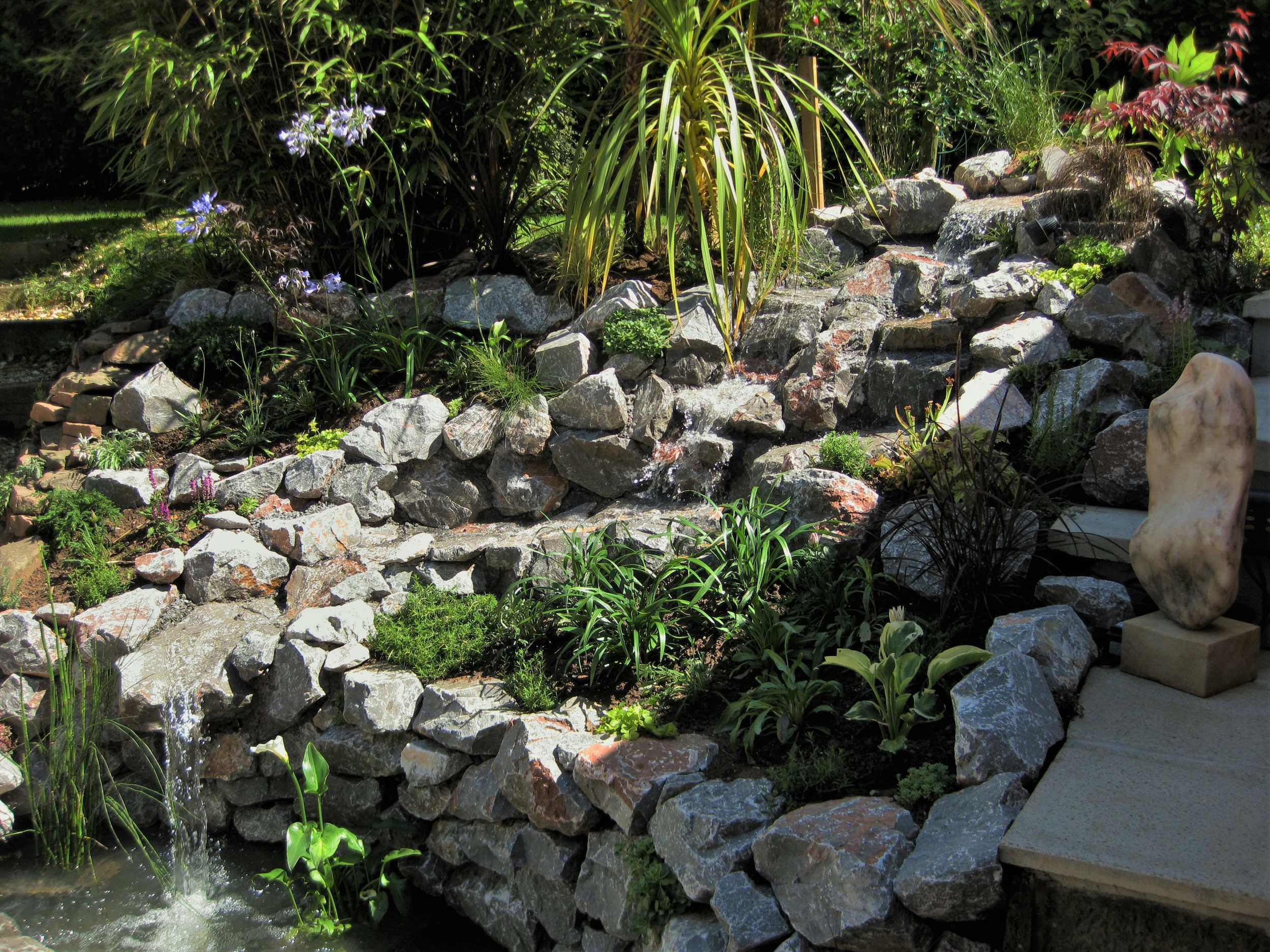 The finished waterscape, tumbling and cascading down before carving into the small fish pond at the bottom.