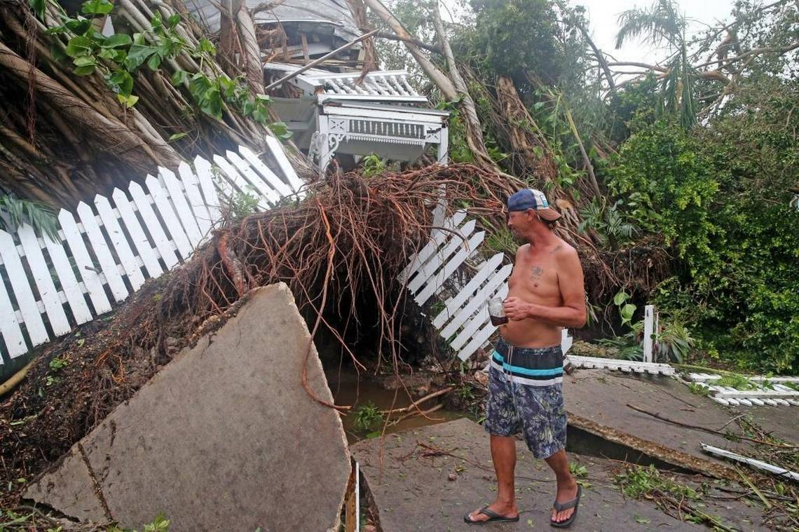 Robert Phillips looks at a house on Williams Street in Key West that was crushed as Hurricane Irma passed over the island, September 10, 2017.  CHARLES TRAINOR JR ctrainor@miamiherald.comy