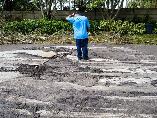 A Collier County worker observes where sewage broke through Mahogany Bend Drive in Naples on Thursday, September 14, 2017.(Photo: Justin Gilliland/Special to the Naples Daily News)
