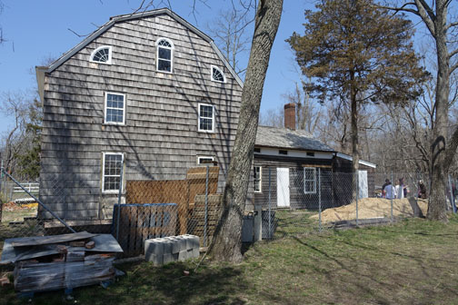 The south side of the house today, facing the millpond.  The quarter round windows at the attic never contained glass, confirmed by historic analysis that shows the painted out black boards are original. Photo from Preservation Long Island's archive.